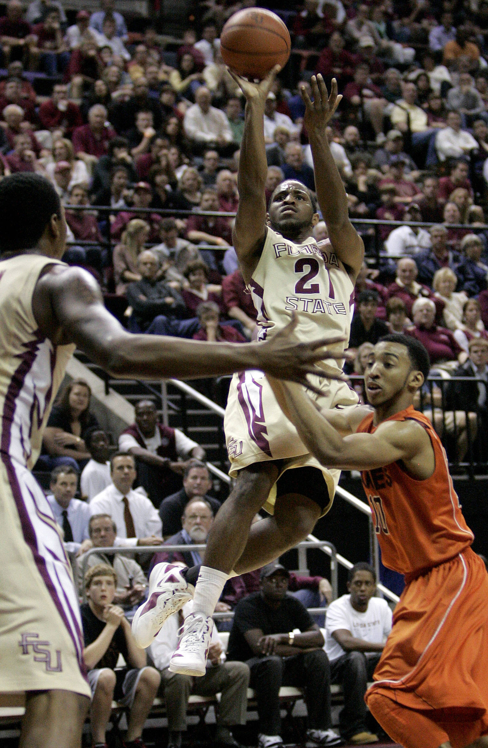 Florida State's Michael Snaer, center, shoots over Virginia Tech's Marquis Rankin, right, during the second half. (AP Photo/Steve Cannon)