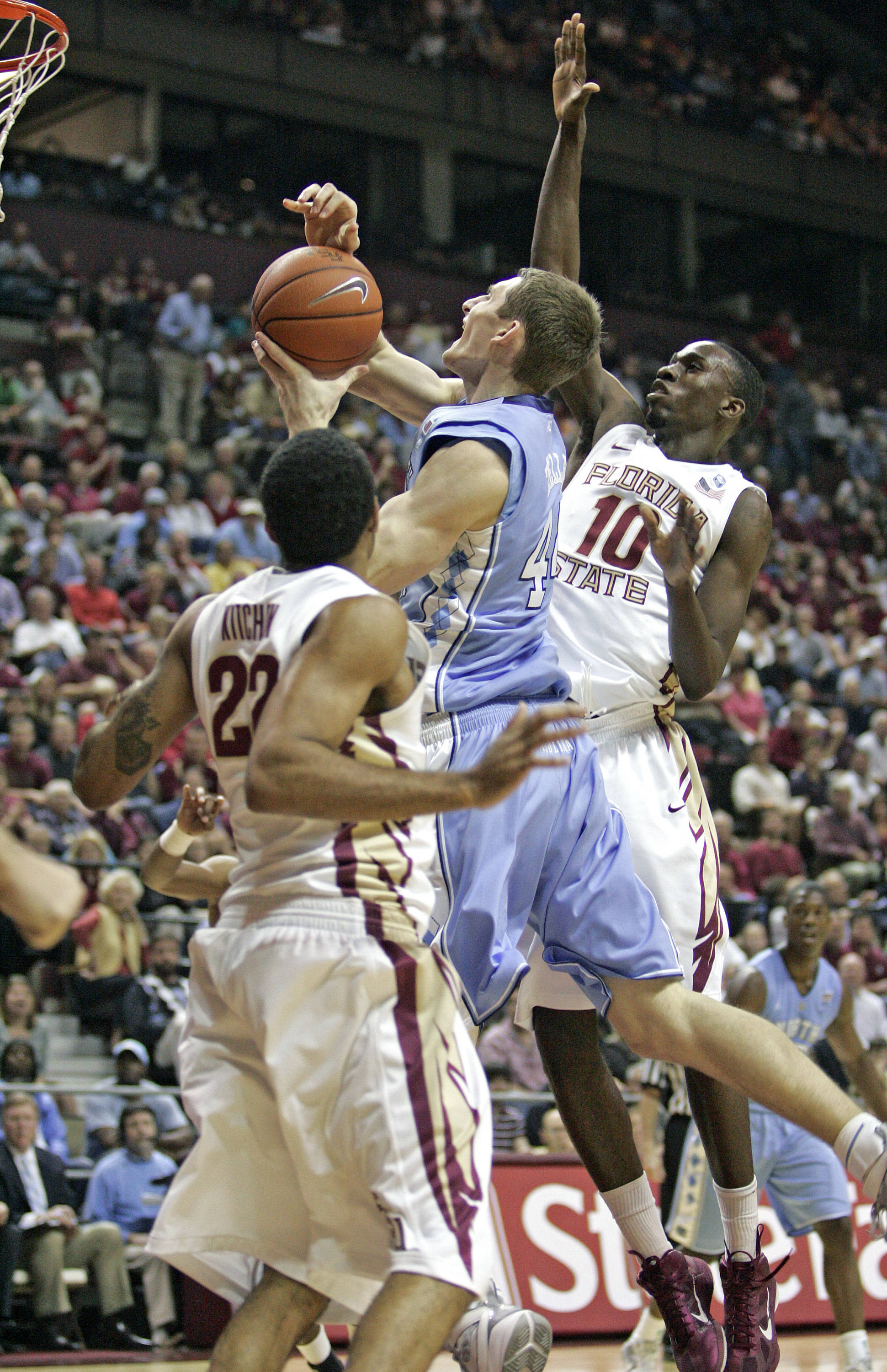Florida State's Derwin Kitchen and Okaro White clog the lane against a driving Tyler Zeller of North Carolina.