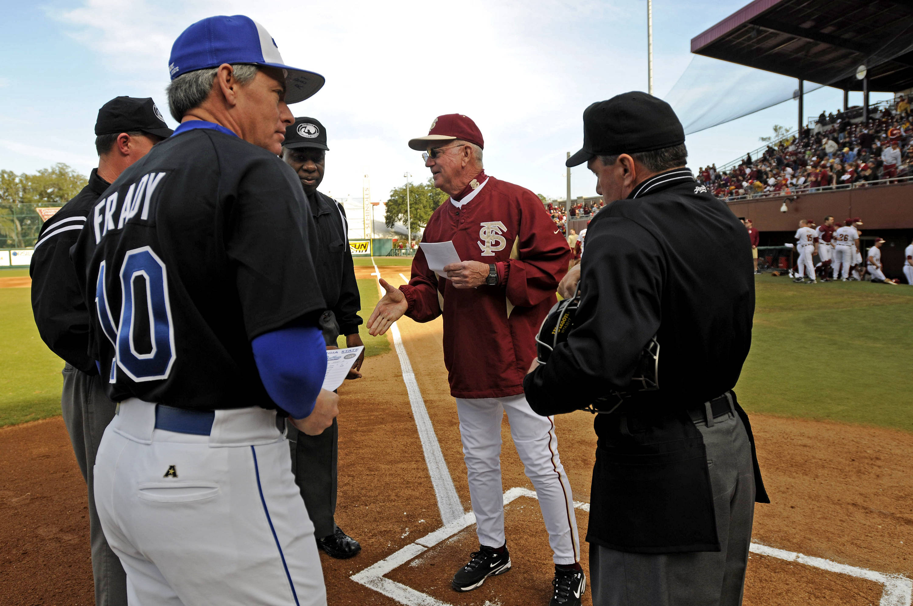 Head coach Mike Martin meets with the umpiring crew and Georgia State head coach Greg Frady.