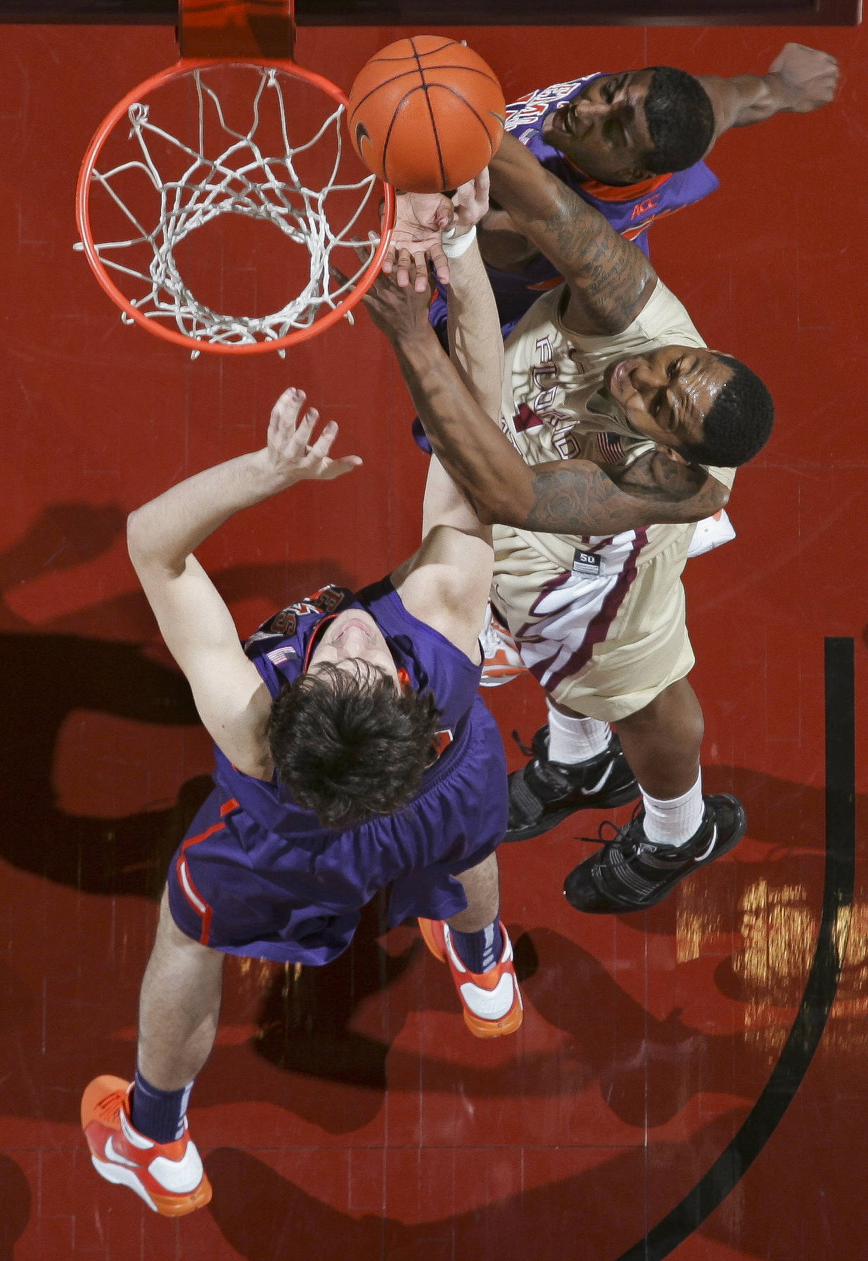Florida State's Xavier Gibson (1) gets between Clemson's Catalin Baciu, bottom, and Devin Coleman, top, for a tip-in during the first half. (AP Photo/Phil Sears)