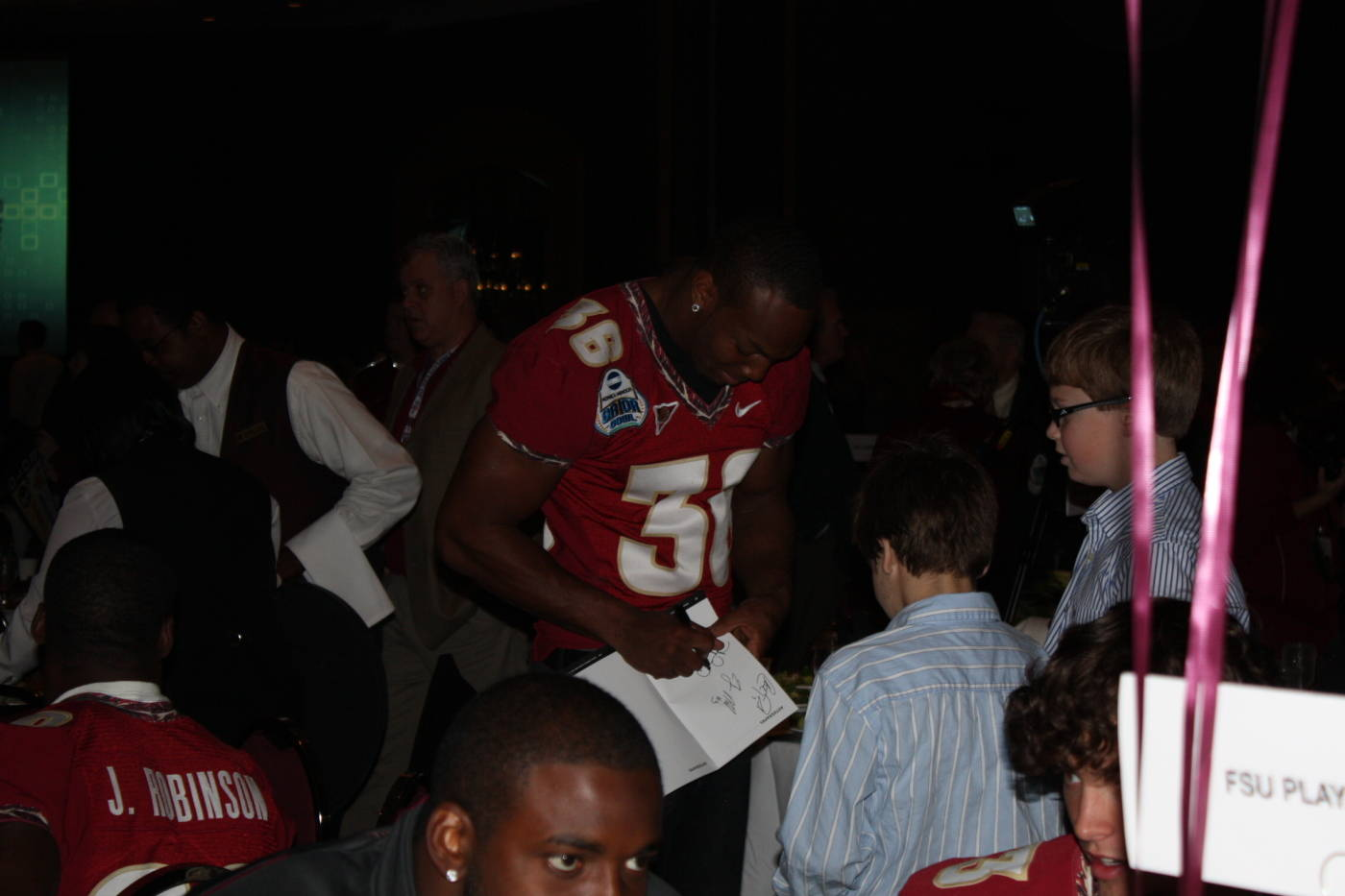 Linebacker Dekoda Watson signing autographs at the Gator Bowl Luncheon and Hall of Fame Induction.