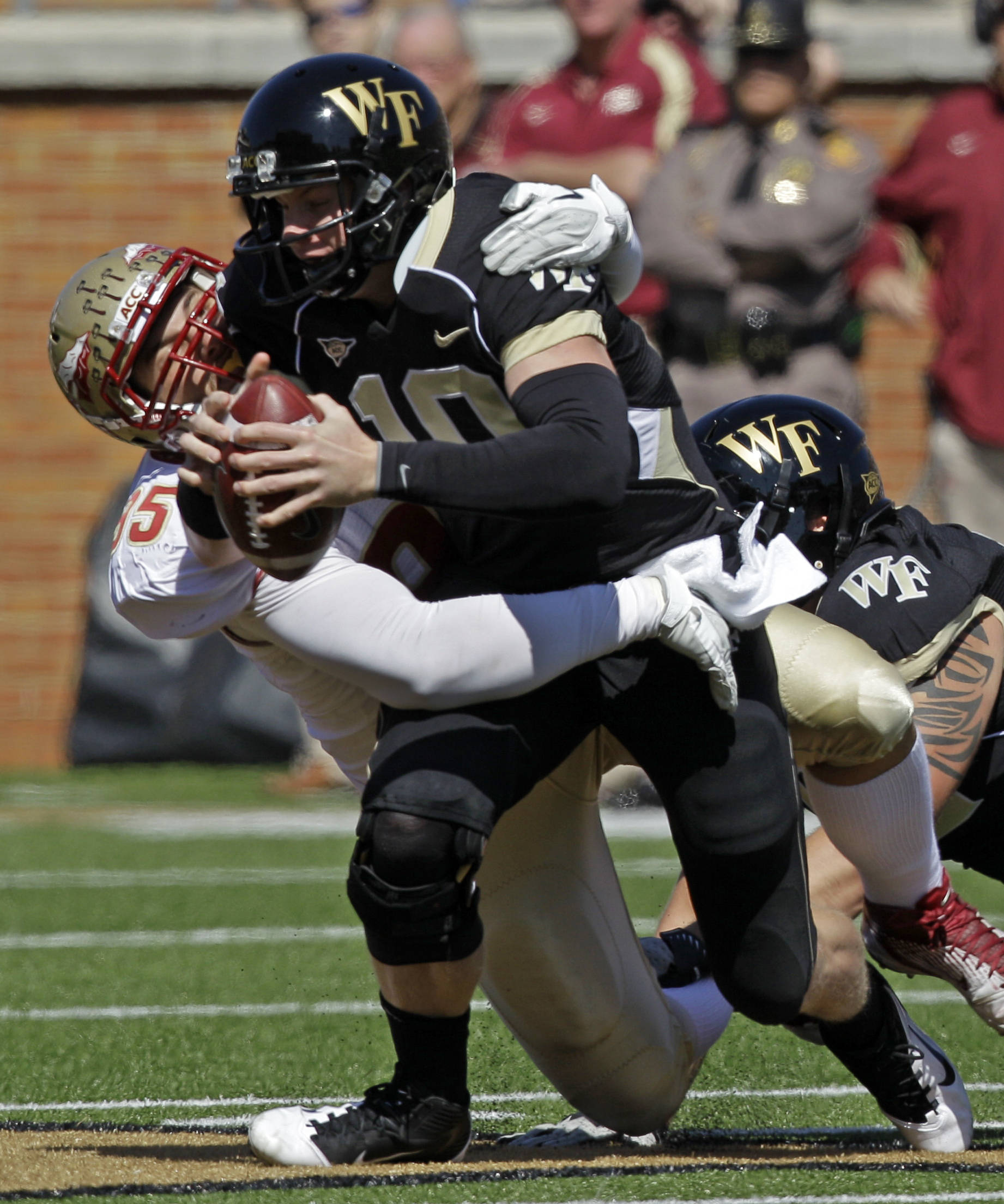 Wake Forest's Tanner Price (10) is sacked by Florida State's Bjoern Werner (95) during the first half of a NCAA college football game in Winston-Salem, N.C., Saturday, Oct. 8, 2011. (AP Photo/Chuck Burton)