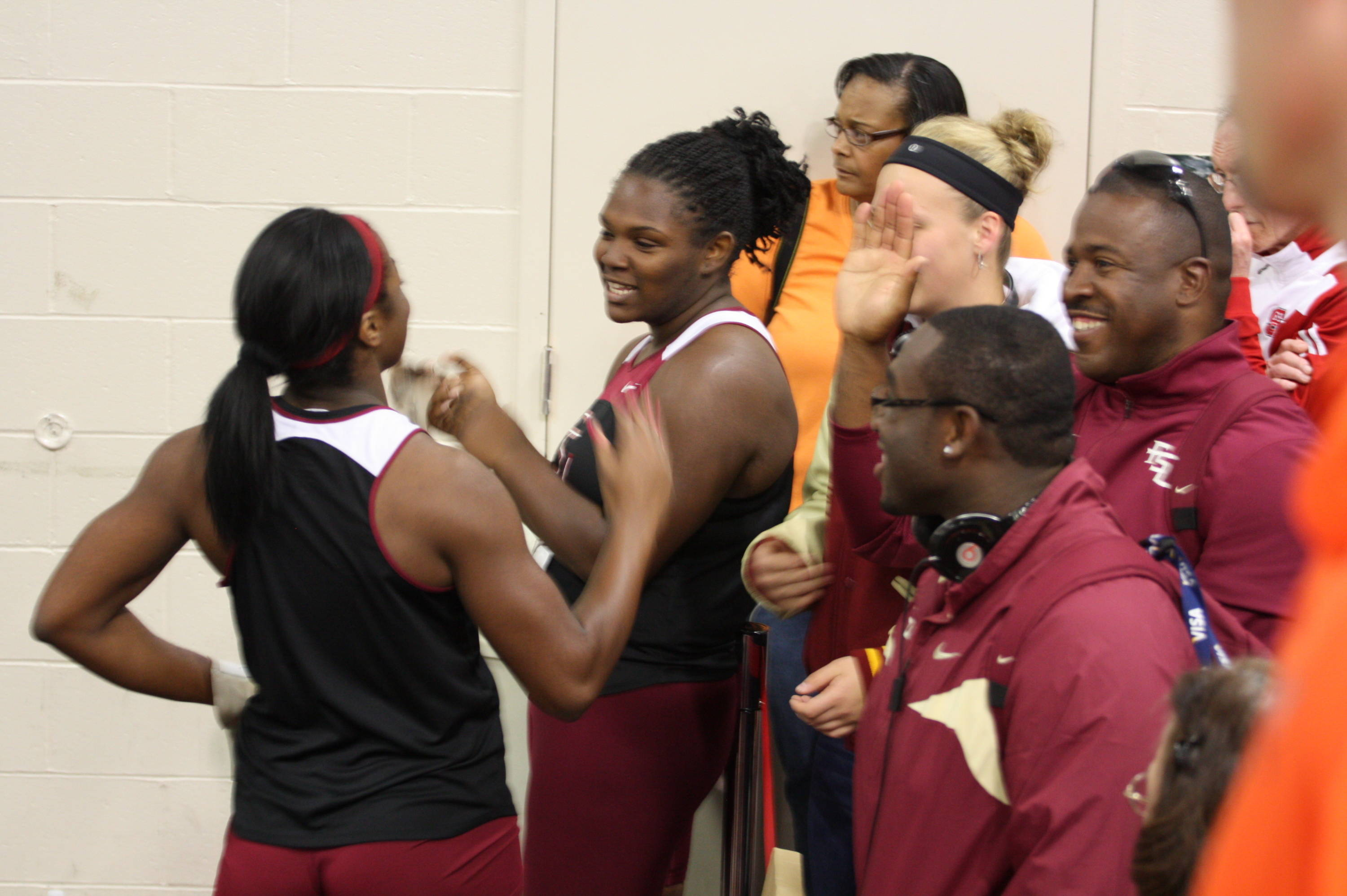 Briana Cherry-Bronson (back to camera) and Lakitta Johnson placed in the weight throw with personal-bests, then celebrated with coach Harlis Meaders and teammates.