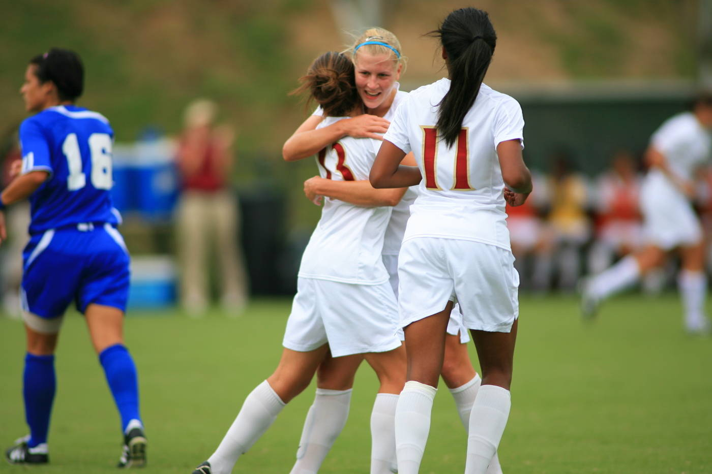 Sanna Talonen, Amanda DaCosta and Casey Short celebrate after a goal.