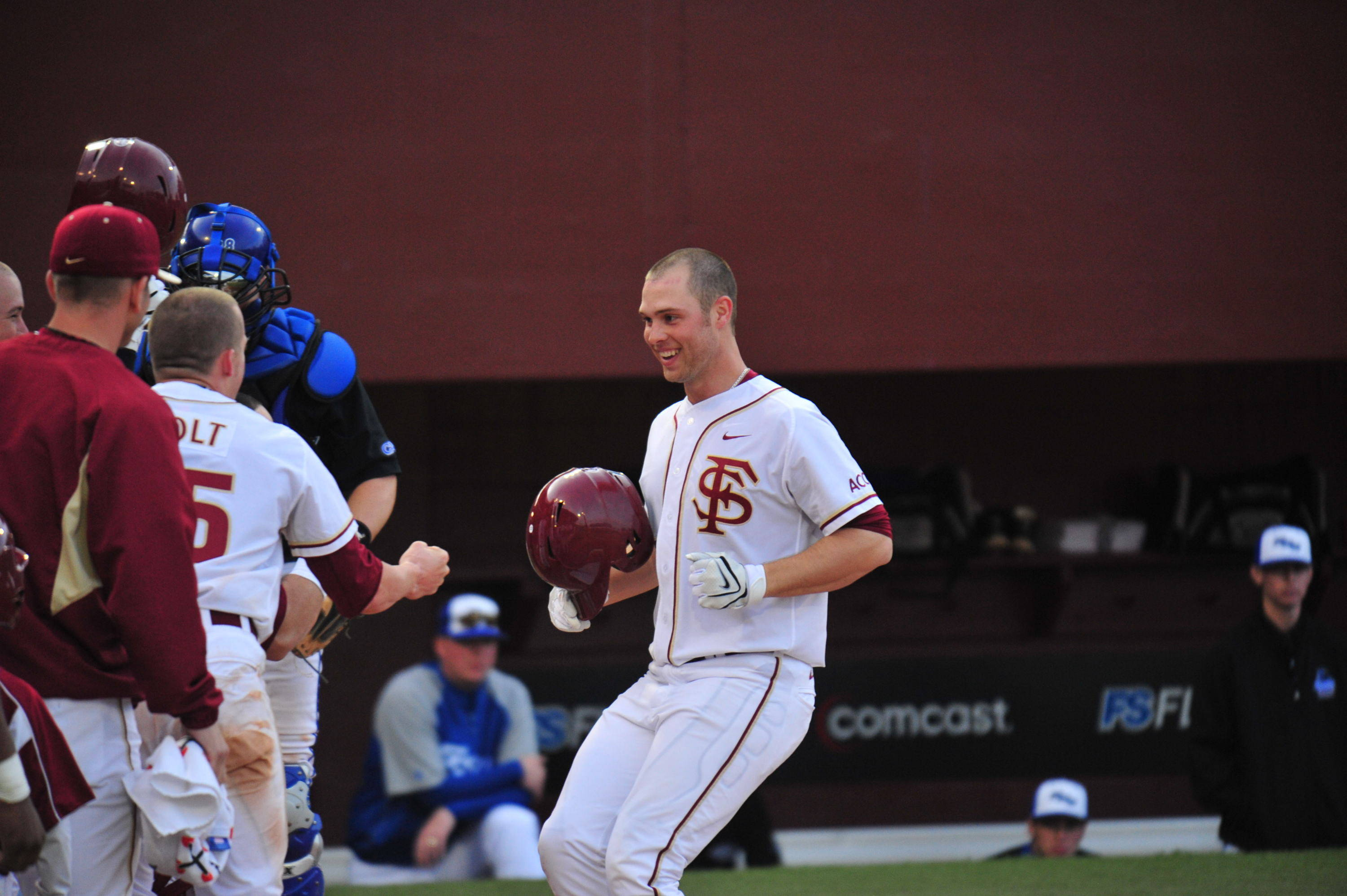Mike McGee celebrates with teammates at home plate after going yard for the first Florida State home run of the season.