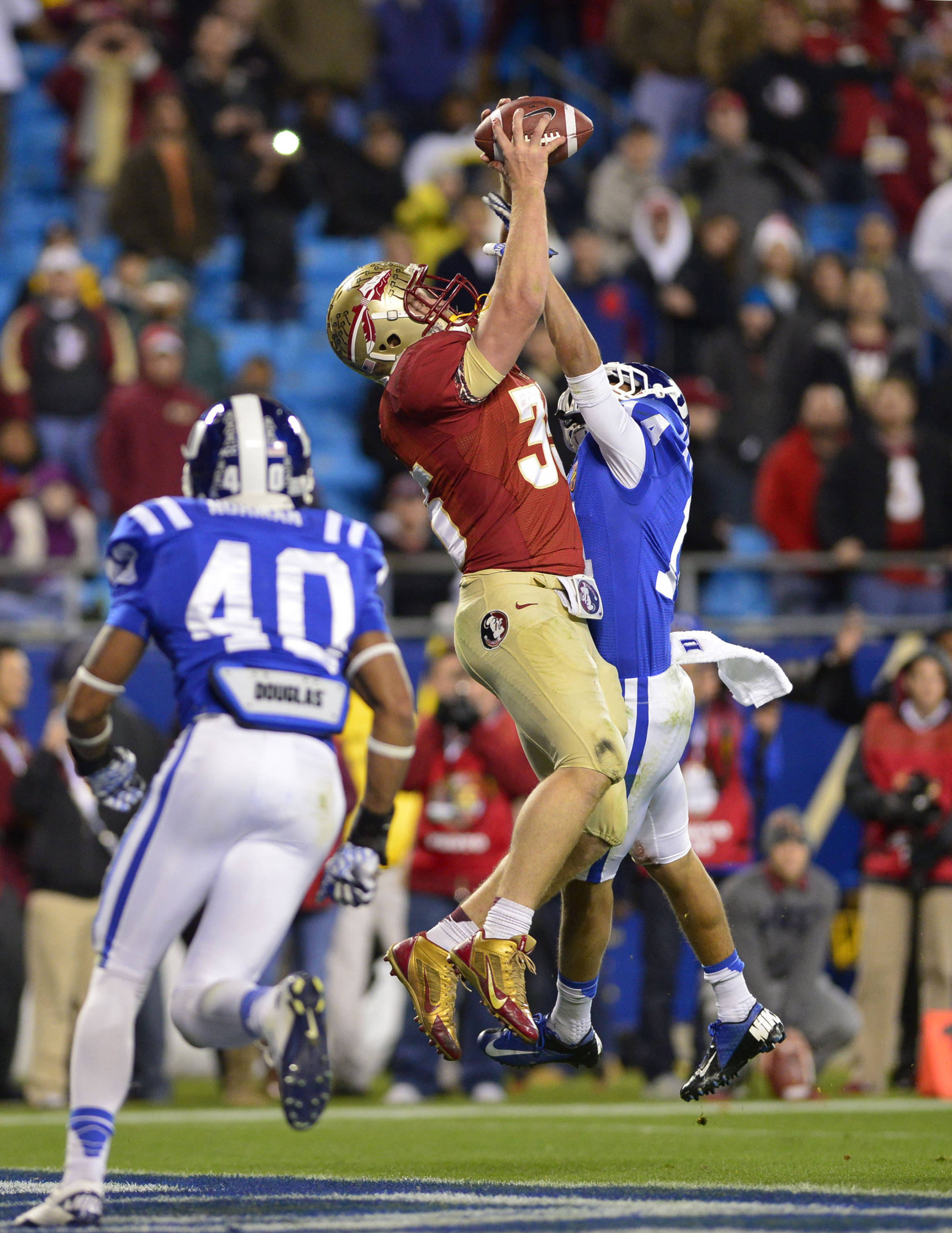 Dec 7, 2013; Charlotte, NC, USA; Florida State Seminoles tight end Nick O'Leary (35) tries to make a catch in the end zone in the fourth quarter as Duke Blue Devils safety Dwayne Norman (40) and cornerback Bryon Fields (14) defend. The Seminoles defeated the Blue Devils 45-7 at Bank of America Stadium. Mandatory Credit: Bob Donnan-USA TODAY Sports