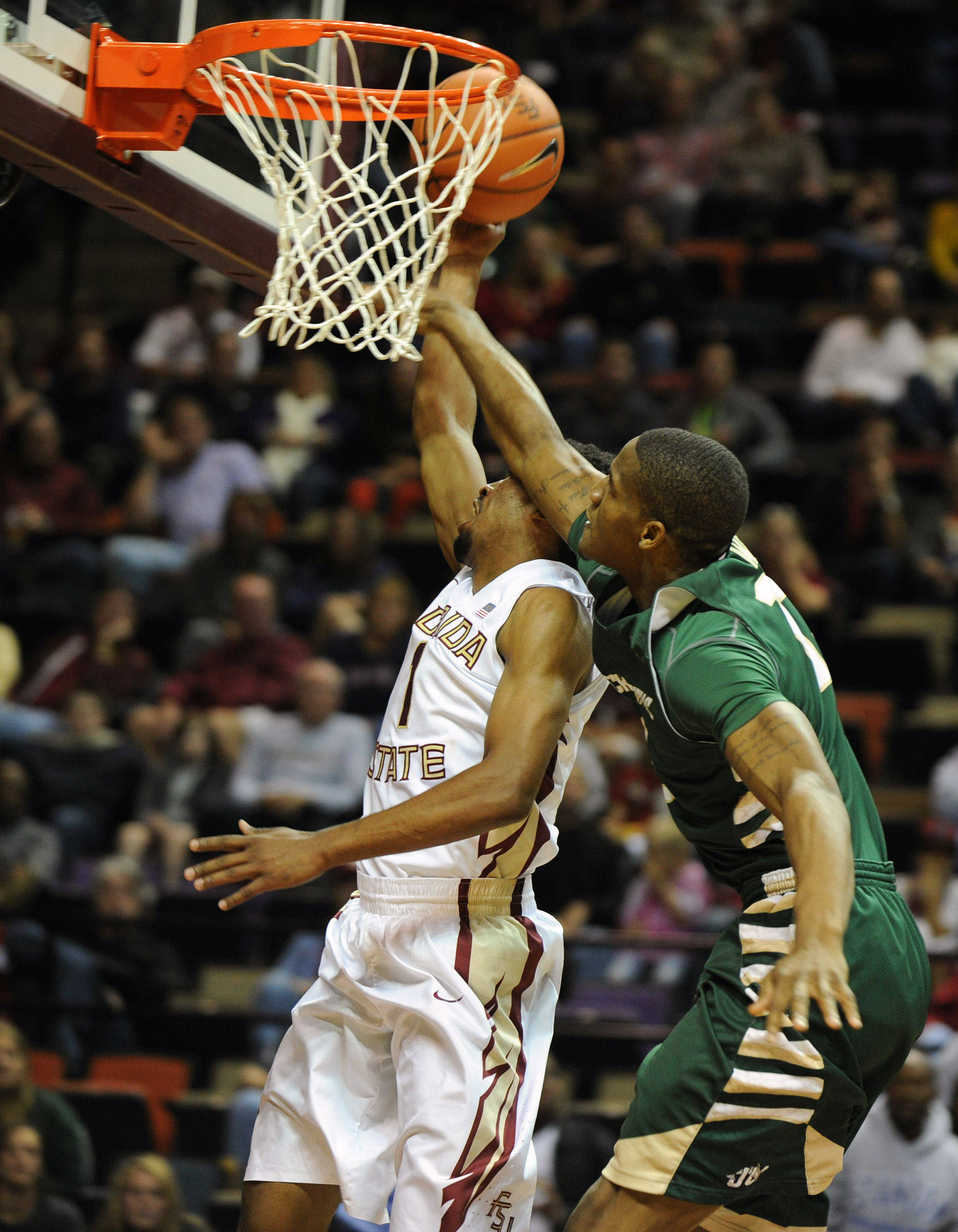 Nov 8, 2013; Tallahassee, FL, USA; Jacksonville Dolphins forward Marcel White (13) fouls Florida State Seminoles guard Devon Bookert (1) as he goes up for a shot during the first half at the Donald L. Tucker Center. Mandatory Credit: Melina Vastola-USA TODAY Sports