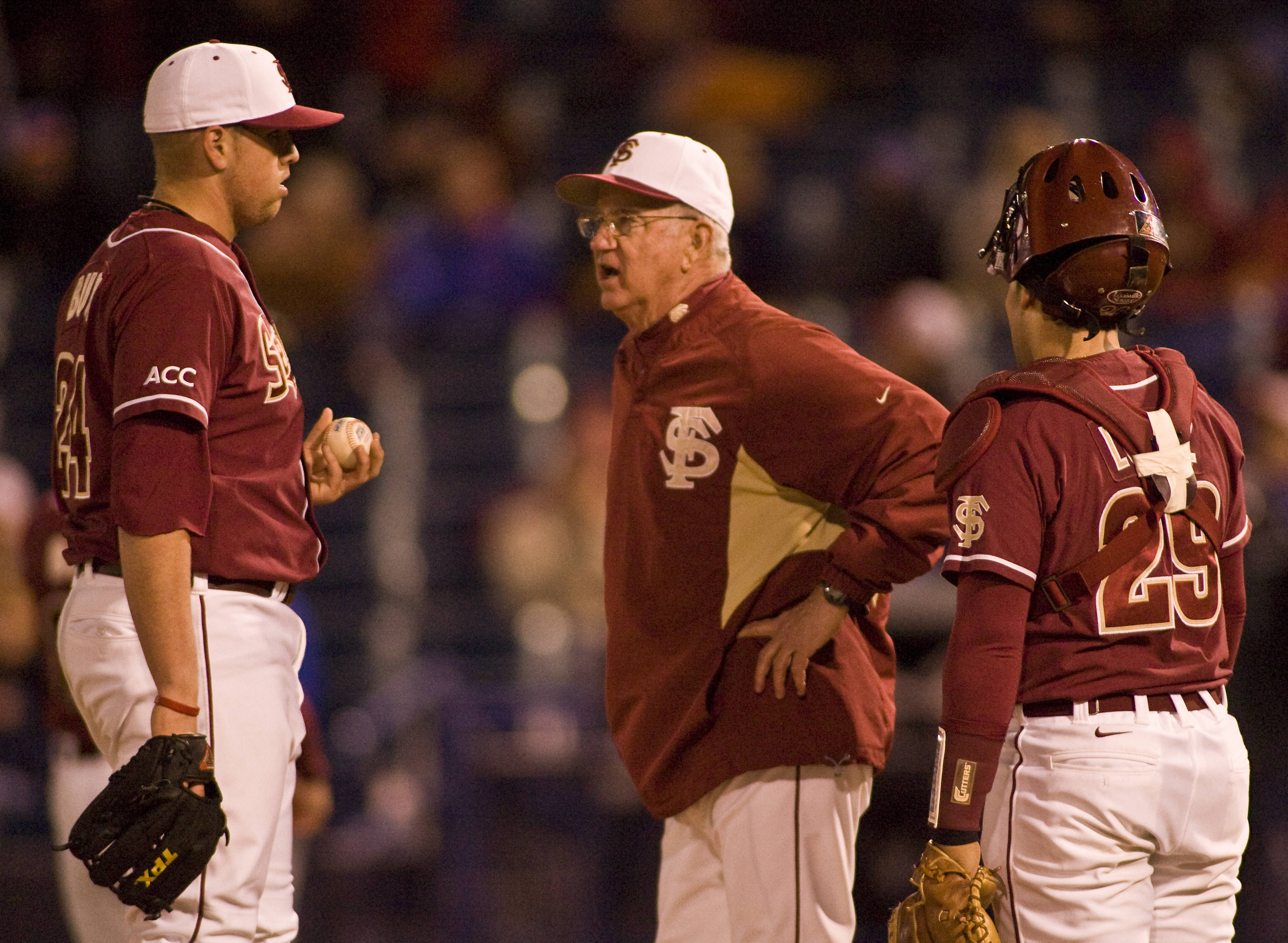 Brian Busch (left) on the mound with head coach Mike Martin and Rafael Lopez