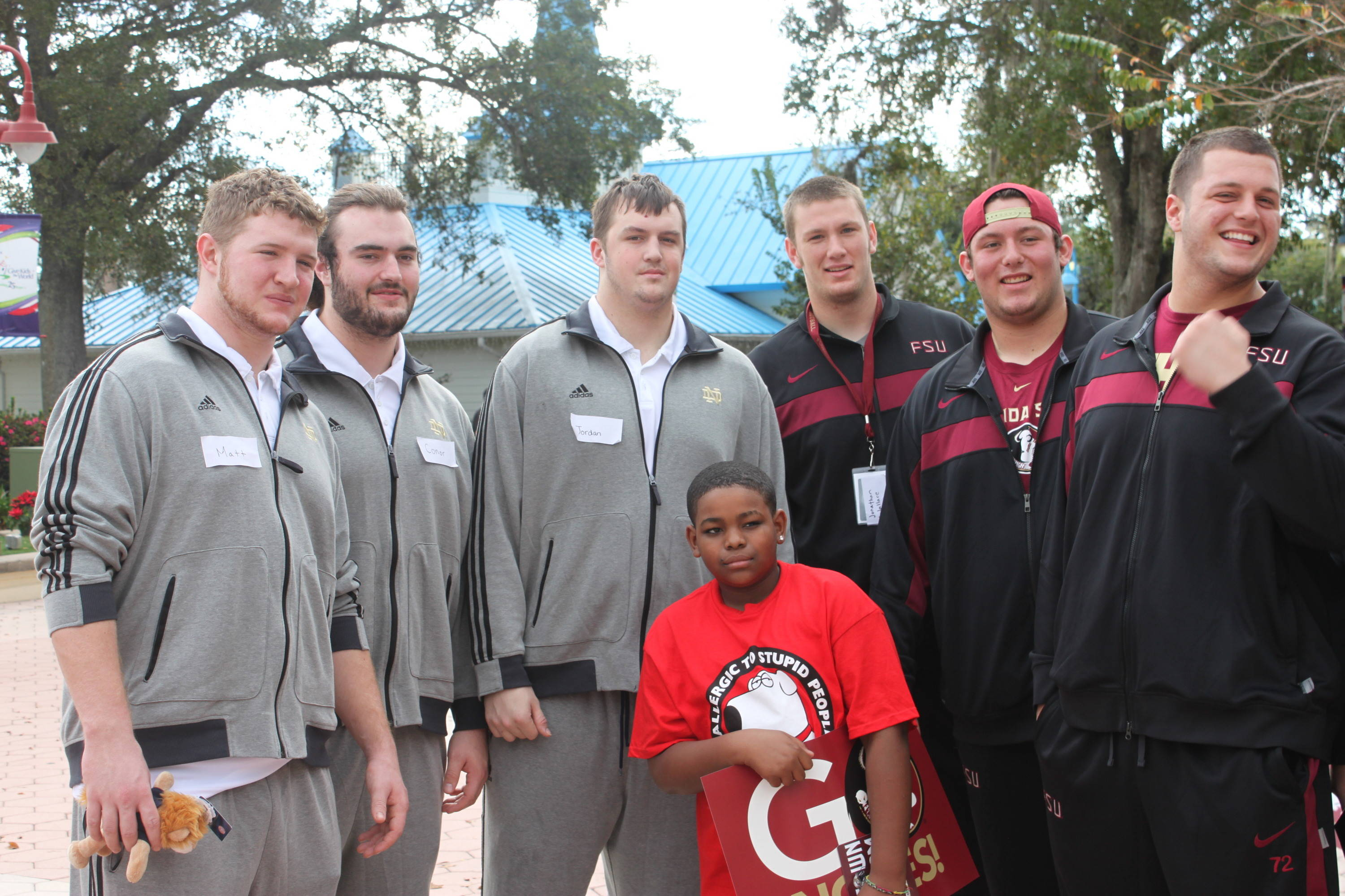 A group of Notre Dame players are joined by a group of 'Noles and a young man.