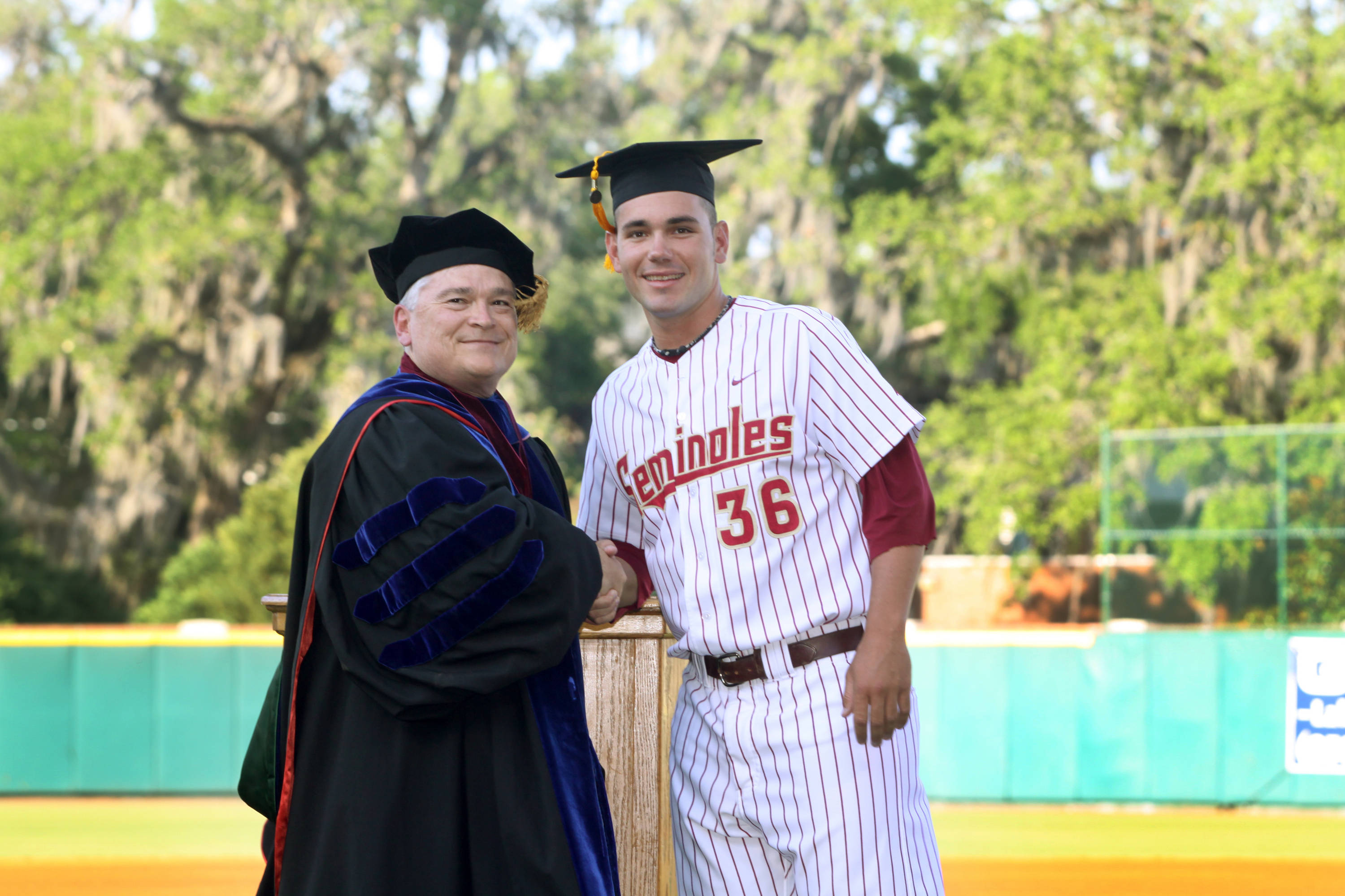 2011 Spring Graduation Ceremony held at Dick Howser Stadium to honor the graduating baseball seniors. Robby Scott (36) with President Barron