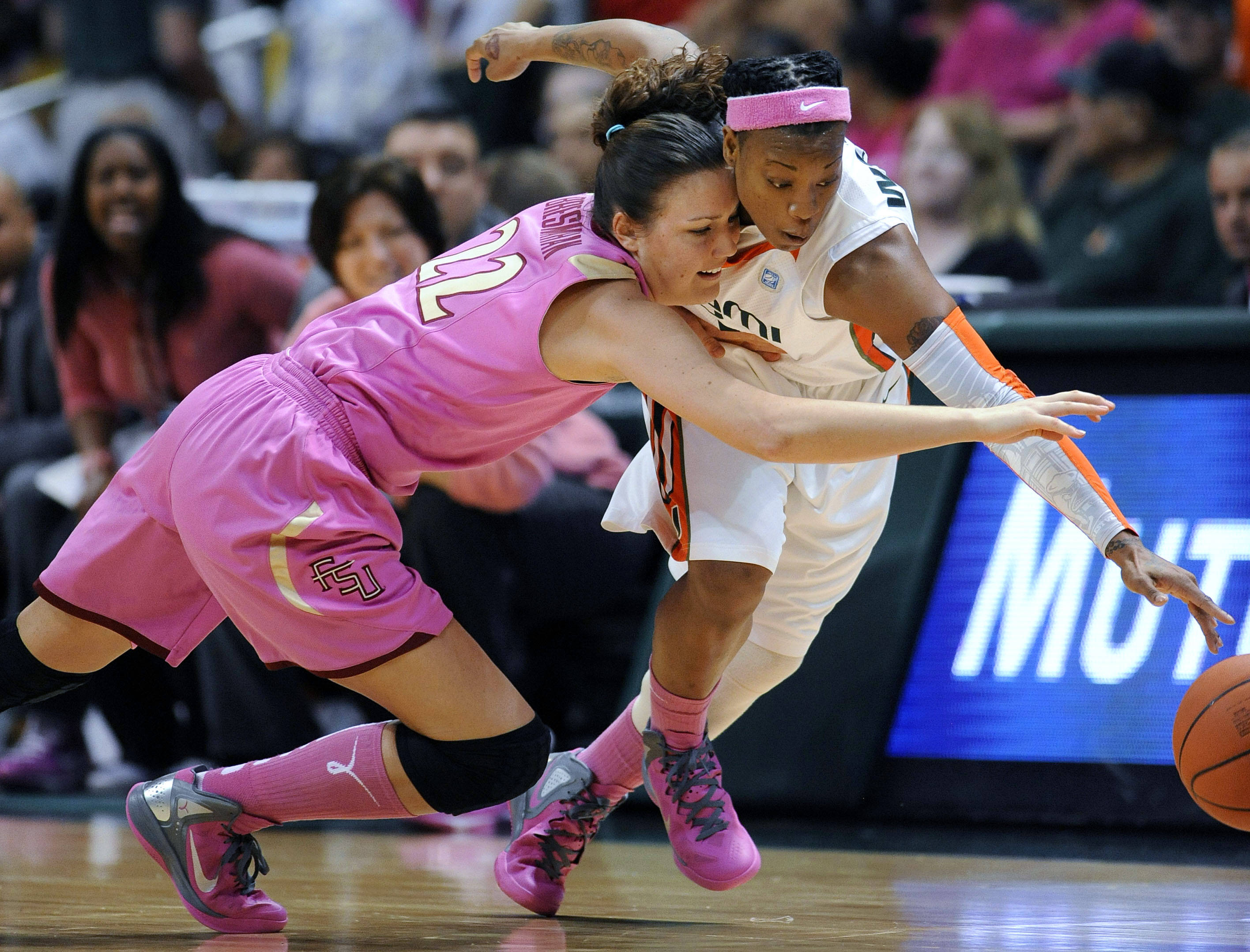 Miami's Riquna Williams, right, and Florida State's Olivia Bresnahan, left, reach for a loose ball during the first half of an NCAA college basketball game on Sunday, Feb. 19, 2012, in Coral Gables, Fla. (AP Photo/Rhona Wise)