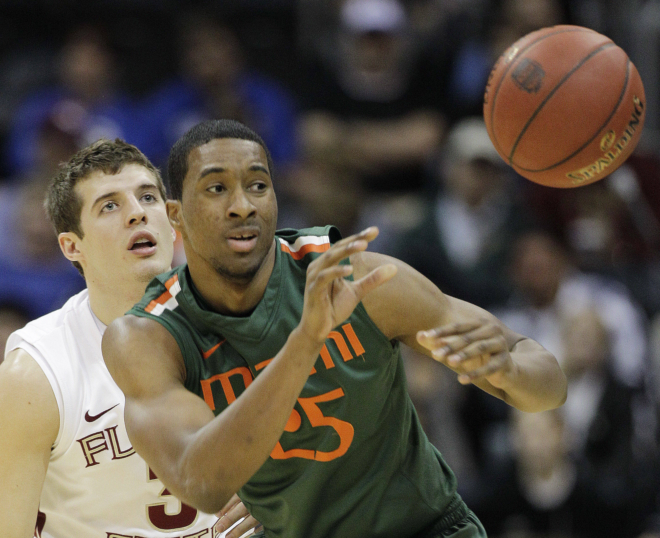 Miami guard Garrius Adams (25) passes the ball ahead of Florida State guard Luke Loucks (3) during the first half of an NCAA college basketball game in the quarterfinals of the Atlantic Coast Conference tournament, Friday, March 9, 2012, in Atlanta. (AP Photo/Chuck Burton)