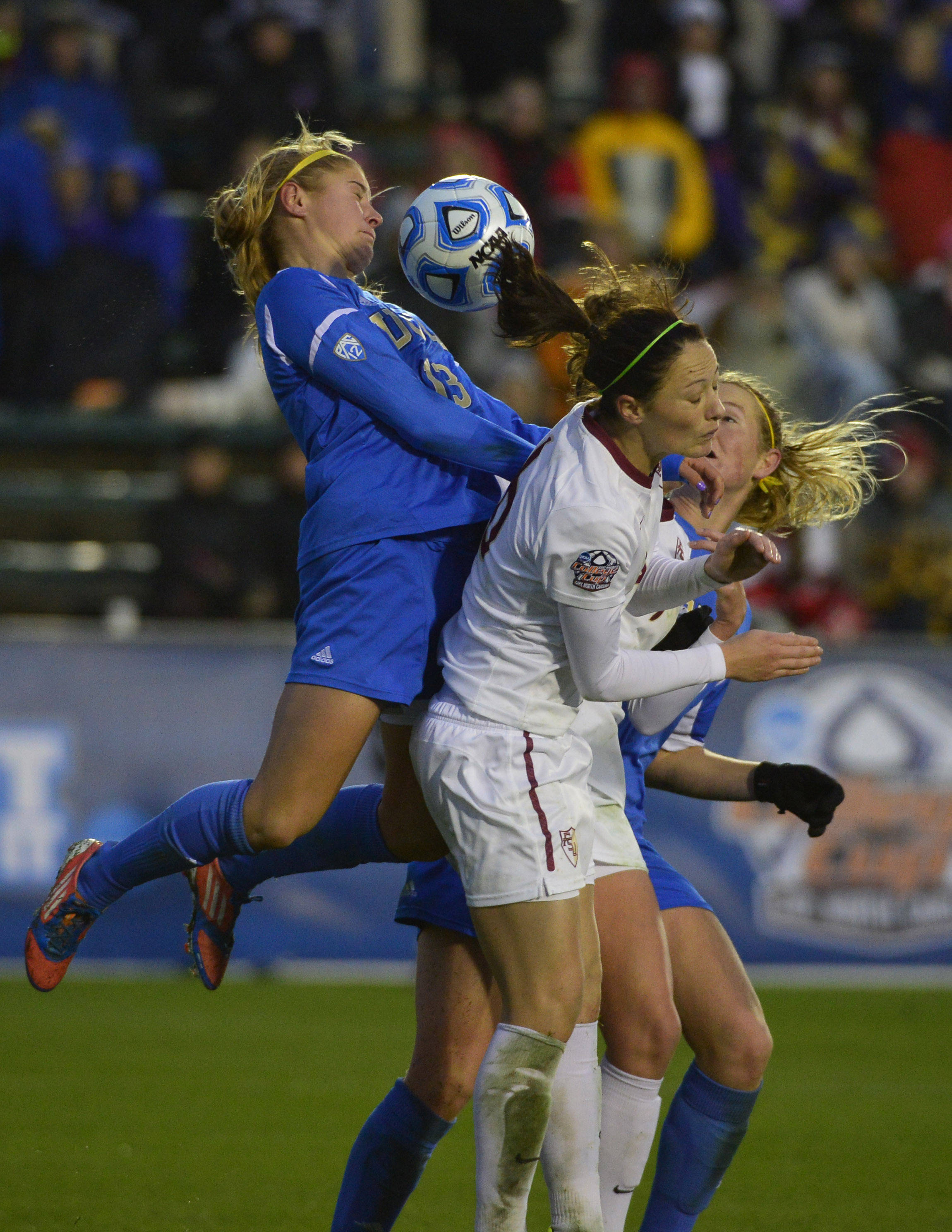 Dec 8, 2013; Cary, NC, USA; UCLA Bruins forward Rosie White (13) and UCLA Bruins midfield/forward Sam Mewis (22) and Florida State Seminoles defender Megan Campbell (6) go up to head the ball. The Bruins defeated the Seminoles 1-0 in overtime at WakeMed Soccer Park. Mandatory Credit: Bob Donnan-USA TODAY Sports
