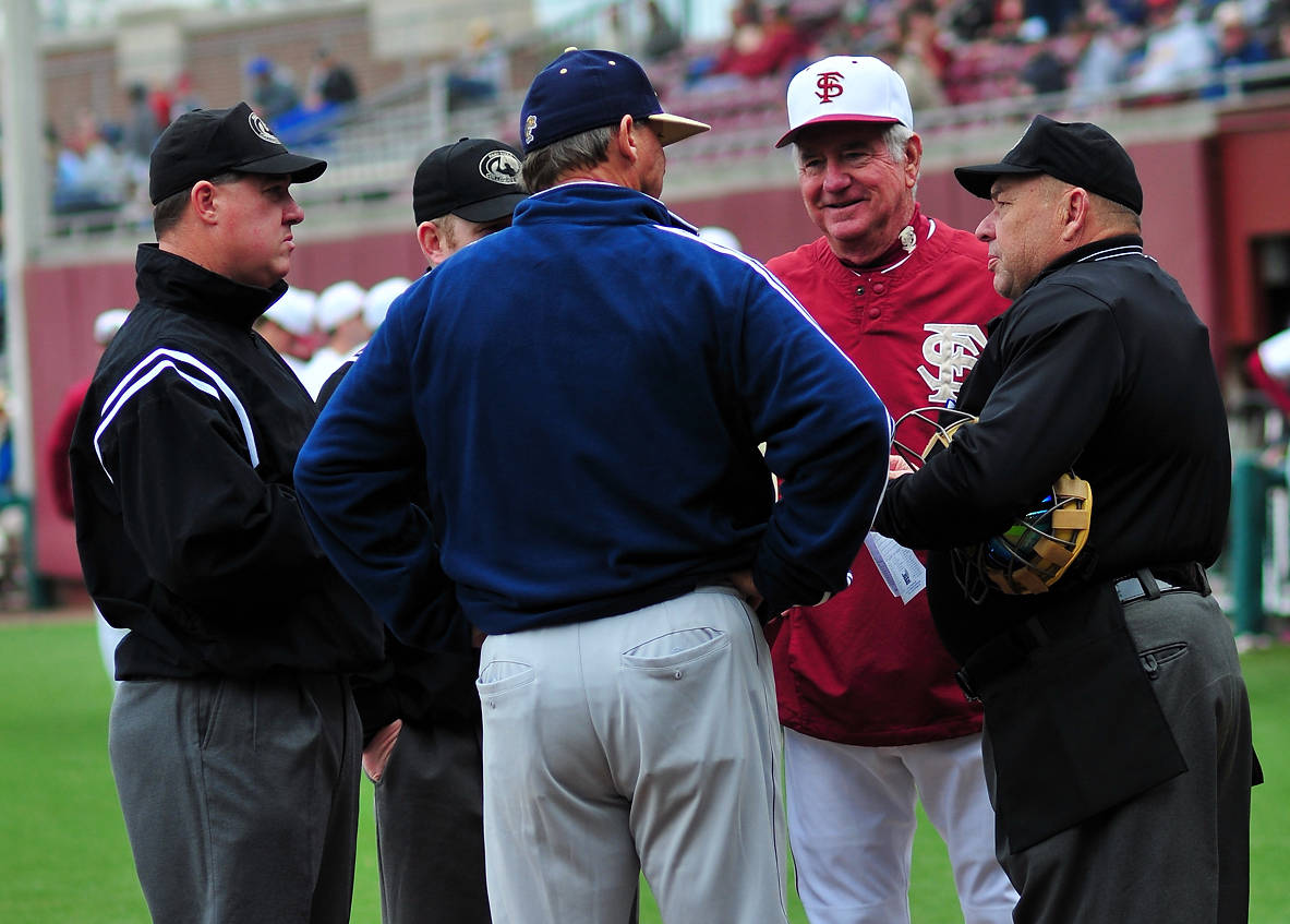 FSU head coach Mike Martin and FIU head coach Turtle Thomas meet with umpires at home plate before the start of Saturday's game.