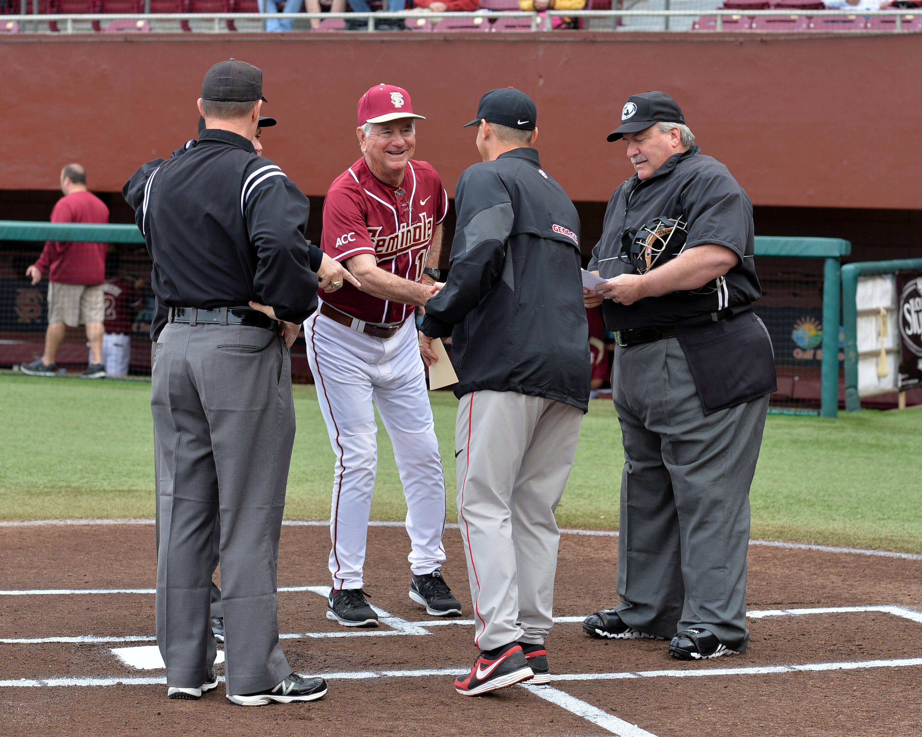 Head coach Mike Martin meets with the umpires and Georgia head coach Scott Stricklin before the start of Friday's game.