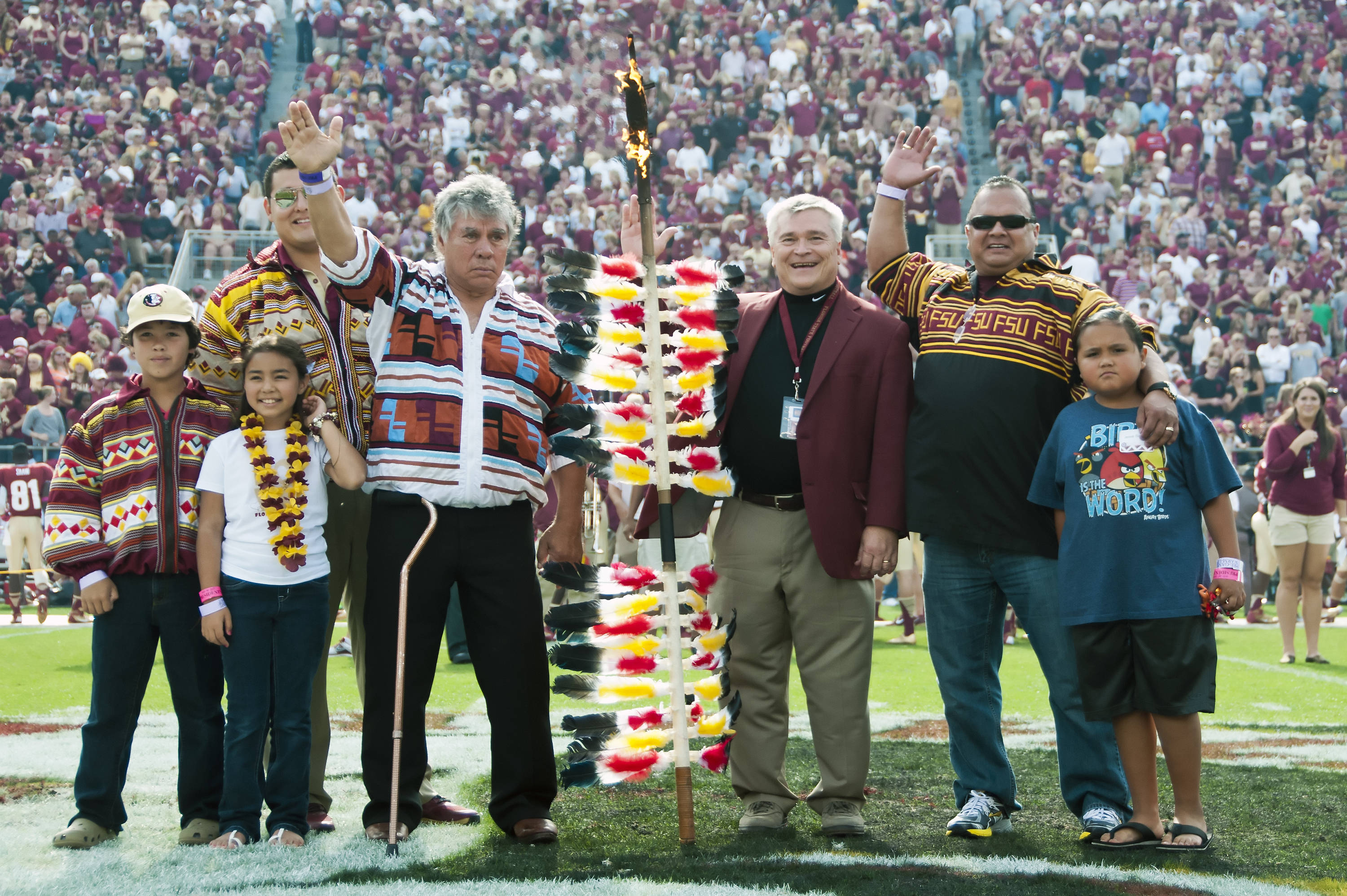 Chief Billie, members of the Seminole tribe and Dr. Alex Barron at midfield