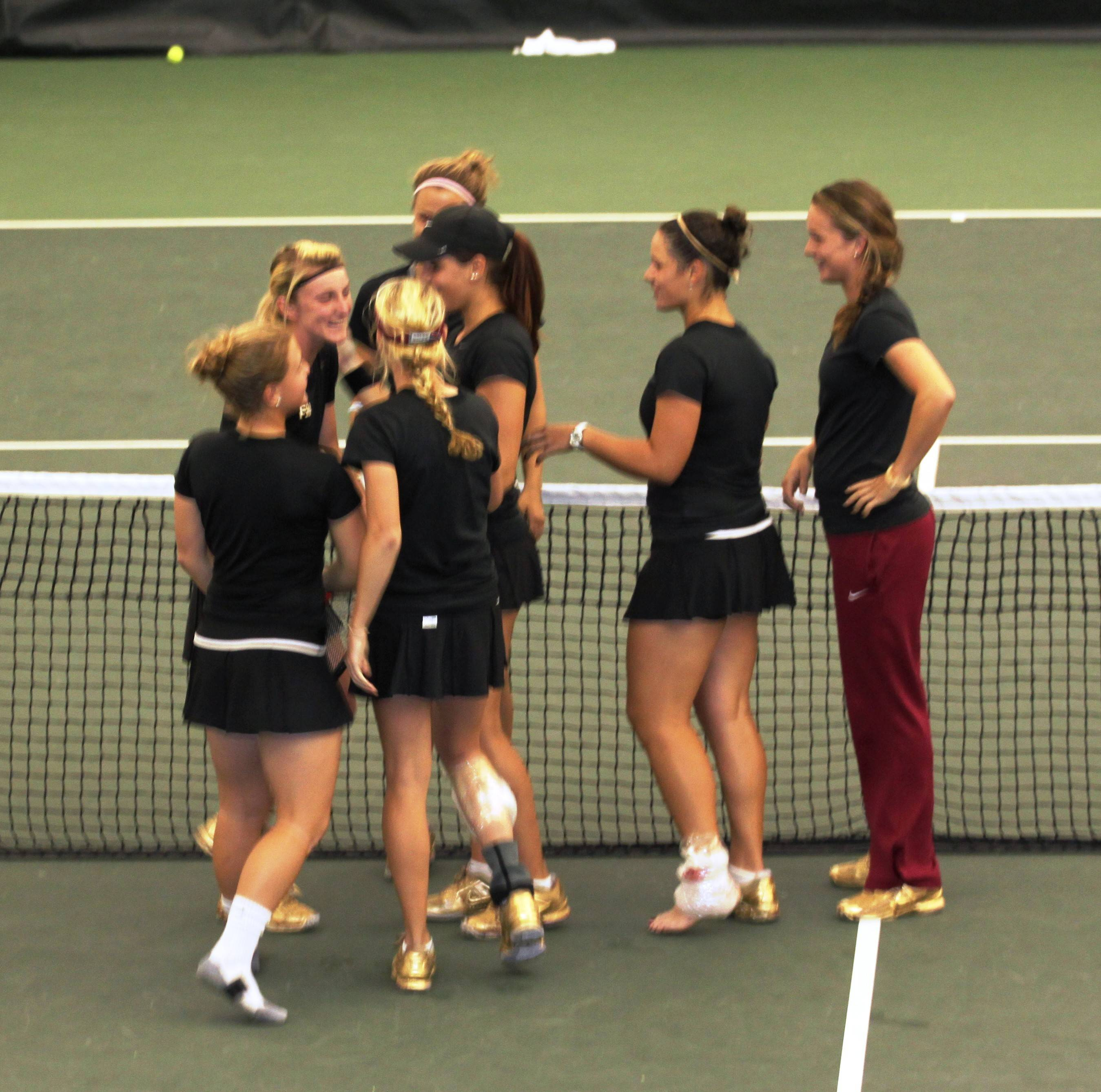 Team swarms Ruth Seaborne after she clinches the match winning point.