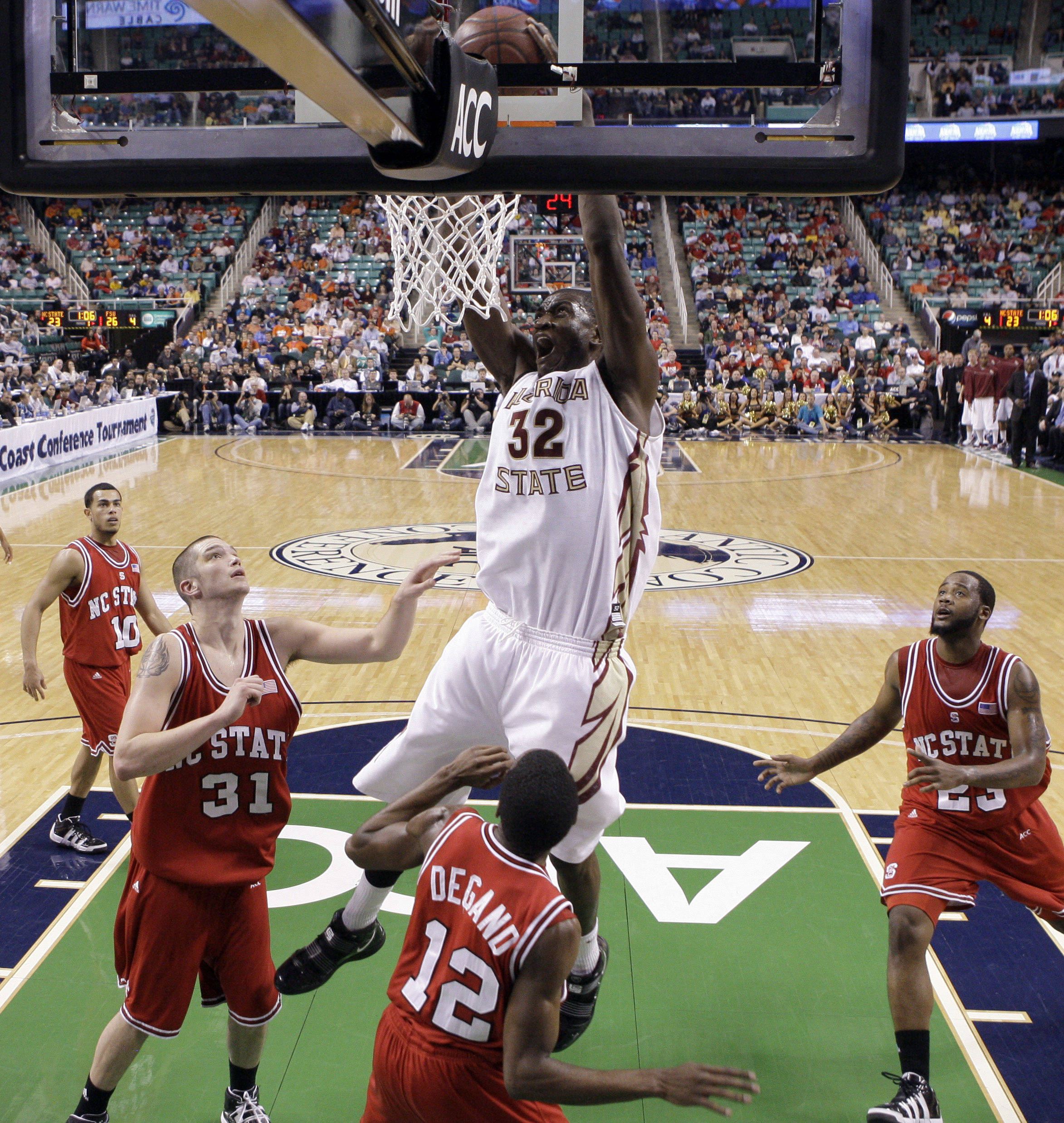 Florida State's Solomon Alabi (32) dunks the ball as North Carolina State's Dennis Horner (31) Farnold Degand (12) and Tracy Smith (23) look on during the first half of an NCAA college basketball game in the Atlantic Coast Conference tournament in Greensboro, N.C., Friday, March 12, 2010. (AP Photo/Chuck Burton)