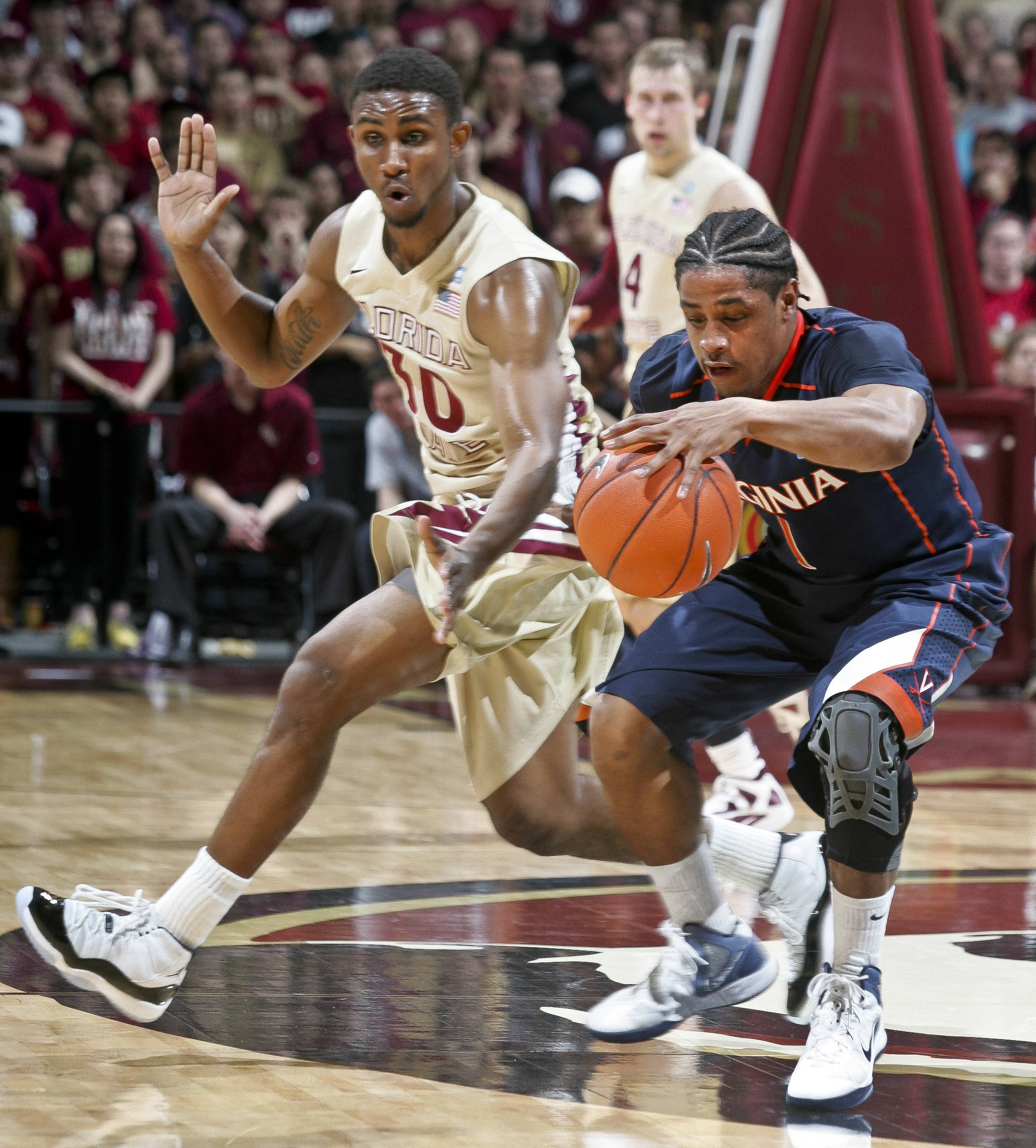 Florida State's Ian Miller (30) goes for a steal on Virginia's Jontel Evans (1) in the first half of an NCAA college basketball game on Saturday, Feb. 4, 2012, in Tallahassee, Fla. Florida State won 58-55. (AP Photo/Phil Sears)