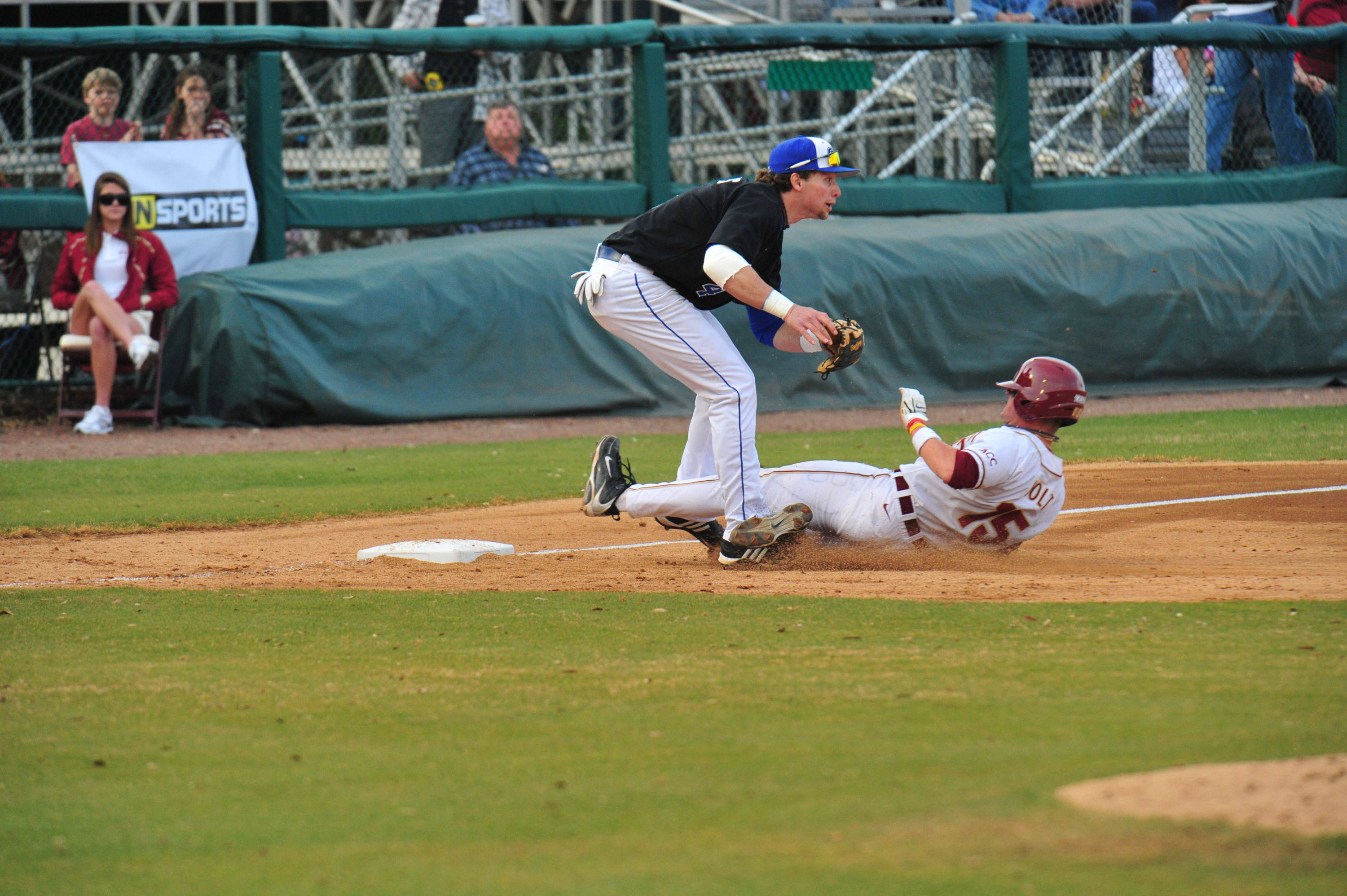 Tyler Holt slides in safely at third base