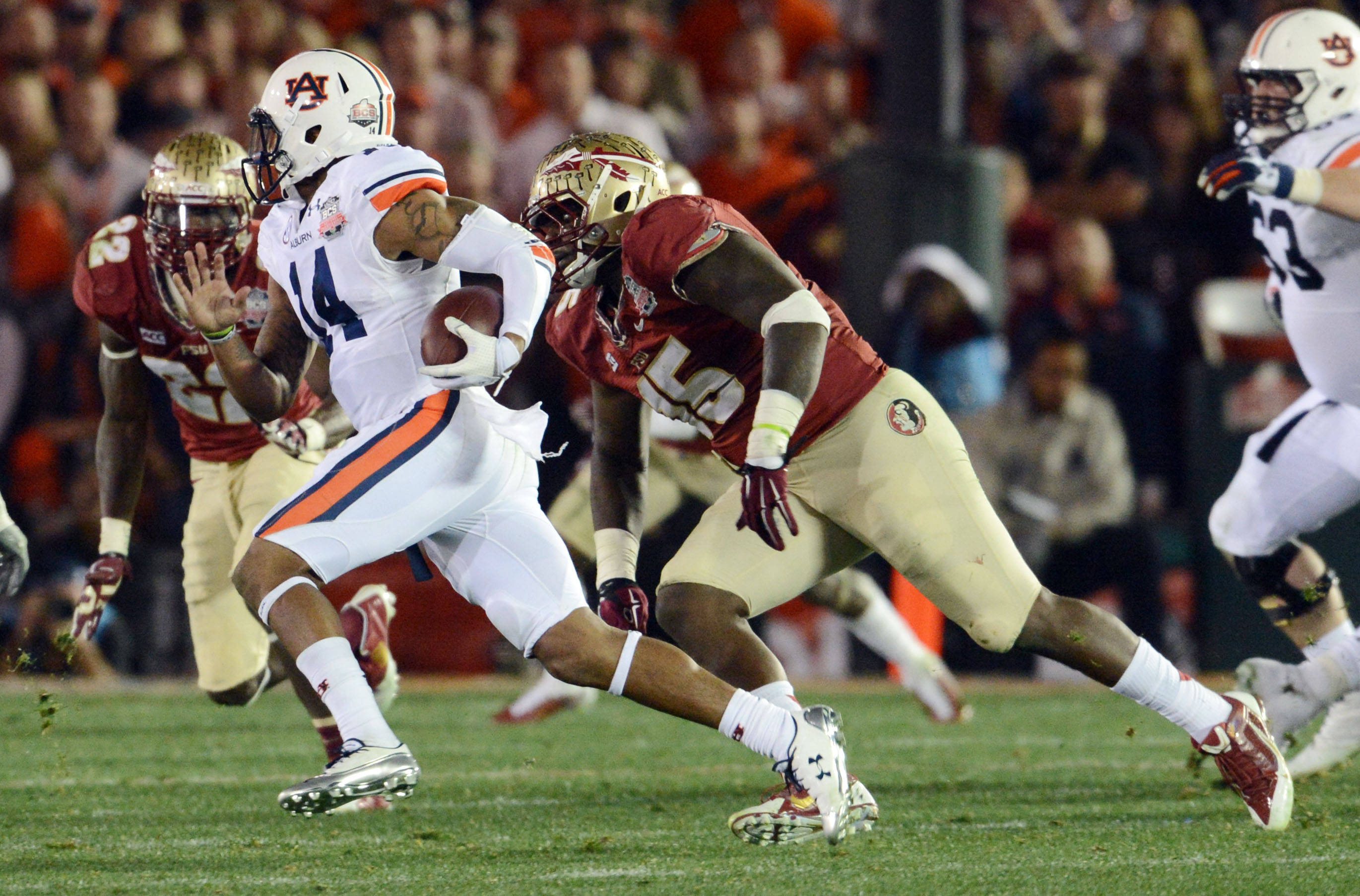 Jan 6, 2014; Pasadena, CA, USA; Auburn Tigers quarterback Nick Marshall (14) runs away from Florida State Seminoles defensive end Mario Edwards Jr. (15) during the first half of the 2014 BCS National Championship game at the Rose Bowl.  Mandatory Credit: Jayne Kamin-Oncea-USA TODAY Sports