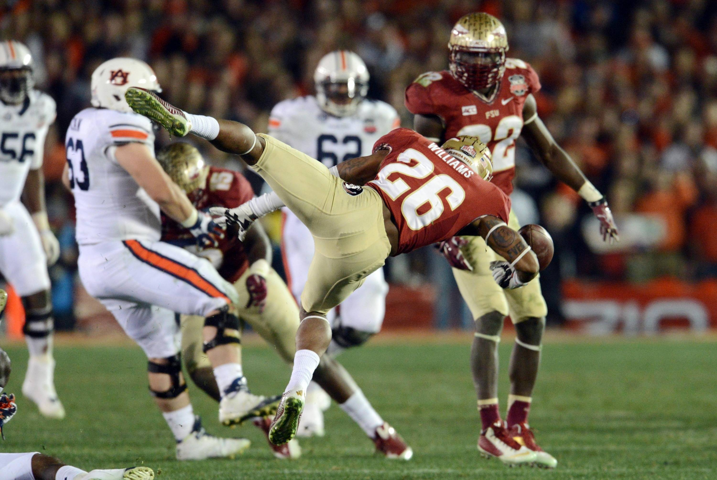 Jan 6, 2014; Pasadena, CA, USA; Florida State Seminoles defensive back P.J. Williams (26) fumbles the ball after intercepting a pass against the Auburn Tigers during the second half of the 2014 BCS National Championship game at the Rose Bowl.  Mandatory Credit: Jayne Kamin-Oncea-USA TODAY Sports