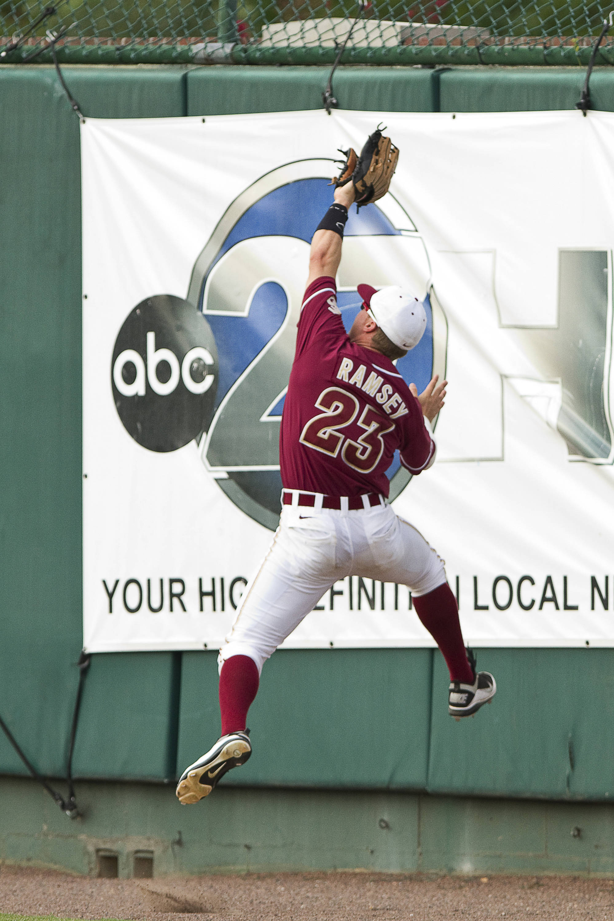 James Ramsey (23) leaps up the wall to catch a pop fly.