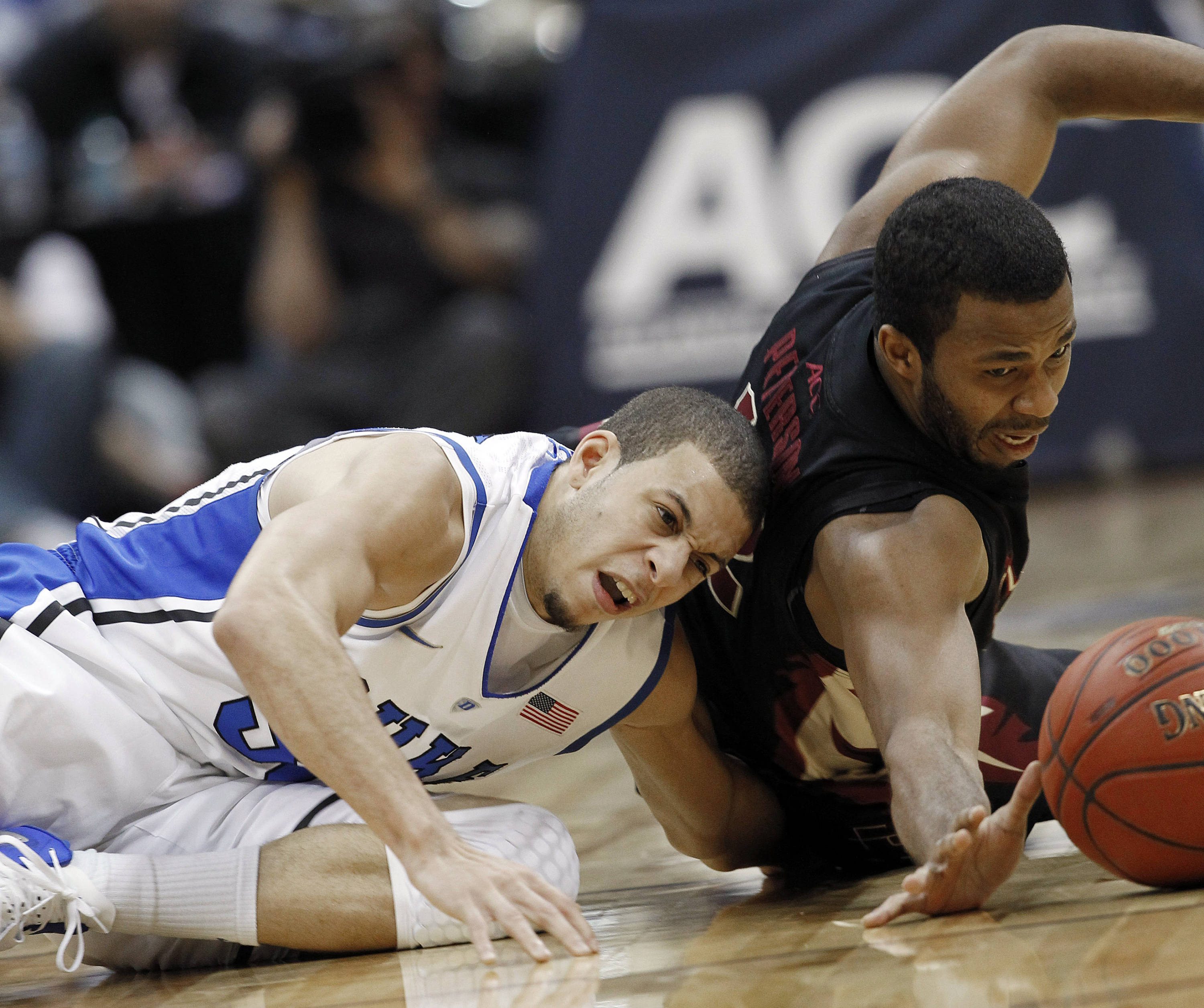 Duke guard Seth Curry (30) and Florida State guard Jeff Peterson (12) fight for a loose ball during the second half of an NCAA college basketball game in the semifinals of the Atlantic Coast Conference tournament, Saturday, March 10, 2012, in Atlanta. (AP Photo/John Bazemore)