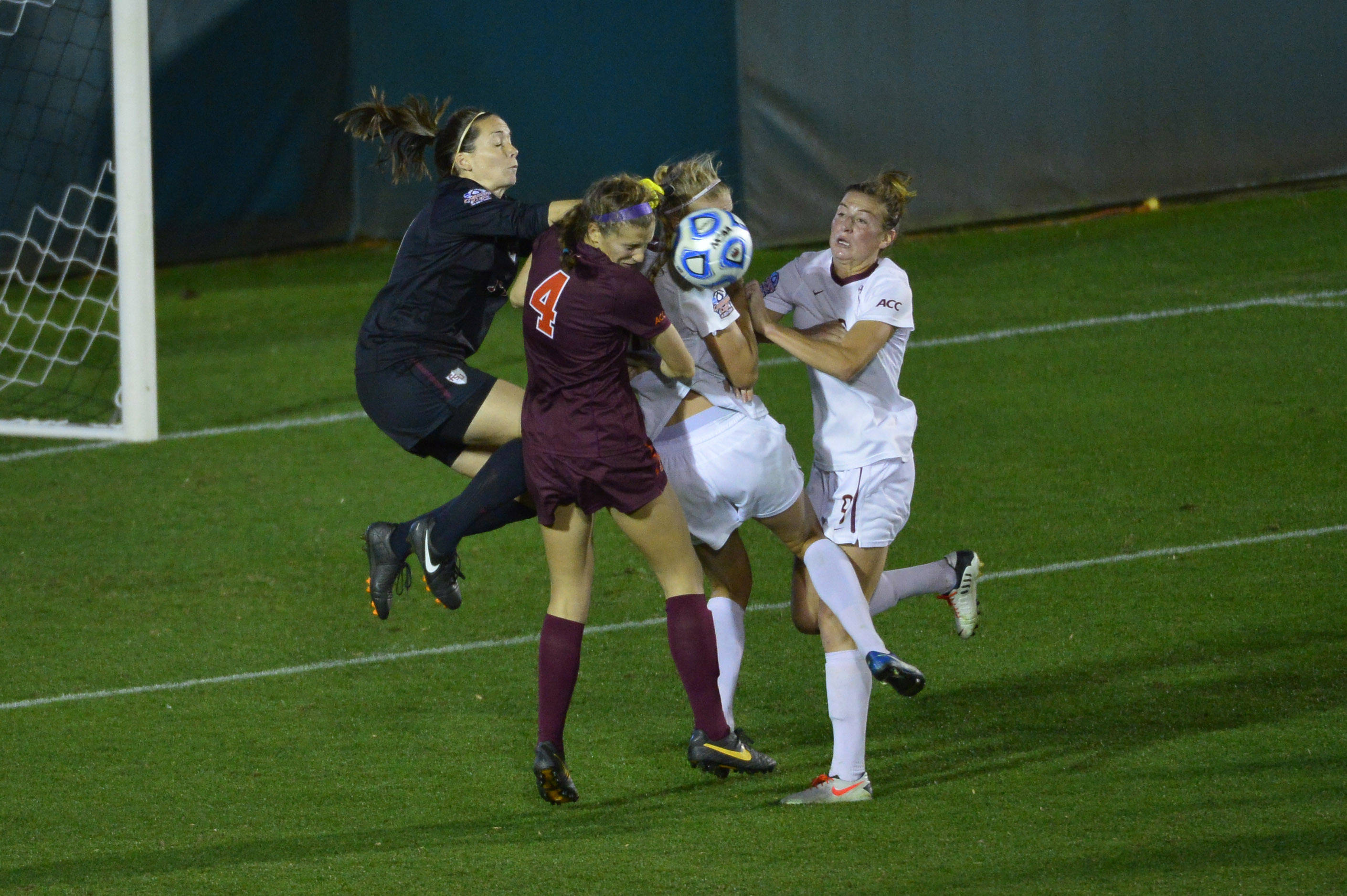 Dec 6, 2013; Cary, NC, USA; Florida State Seminoles goalkeeper Kelsey Wys (19) punches the ball out as midfielder Dagny Brynjarsdottir (7) and defender Kassey Kallman (9) help defend and Virginia Tech Hokies forward Shannon Mayrose (4) goes for the ball in the second half. The Seminoles defeated the Hokies 3-2 at WakeMed Soccer Park. Mandatory Credit: Bob Donnan-USA TODAY Sports