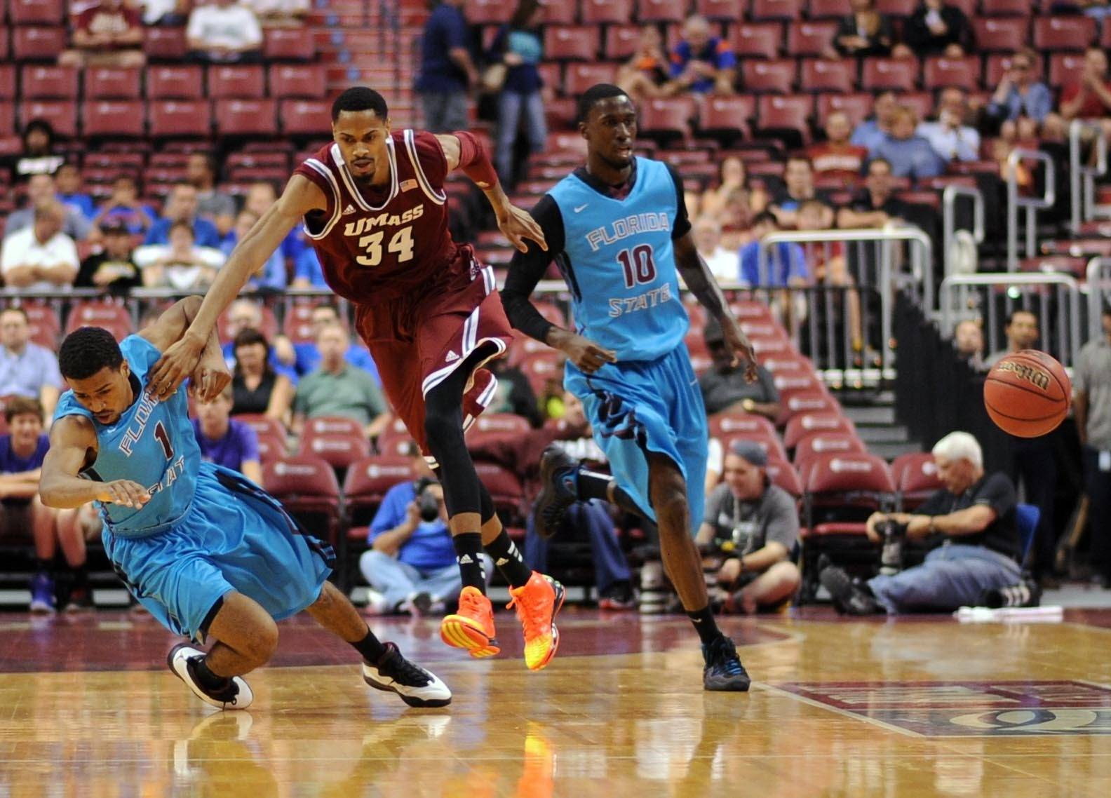 Dec 21, 2013; Sunrise, FL, USA; Florida State Seminoles guard Devon Bookert (left) and Massachusetts Minutemen forward Raphiael Putney (center) chase a loose ball during the first half at BB&T Center. Mandatory Credit: Steve Mitchell-USA TODAY Sports