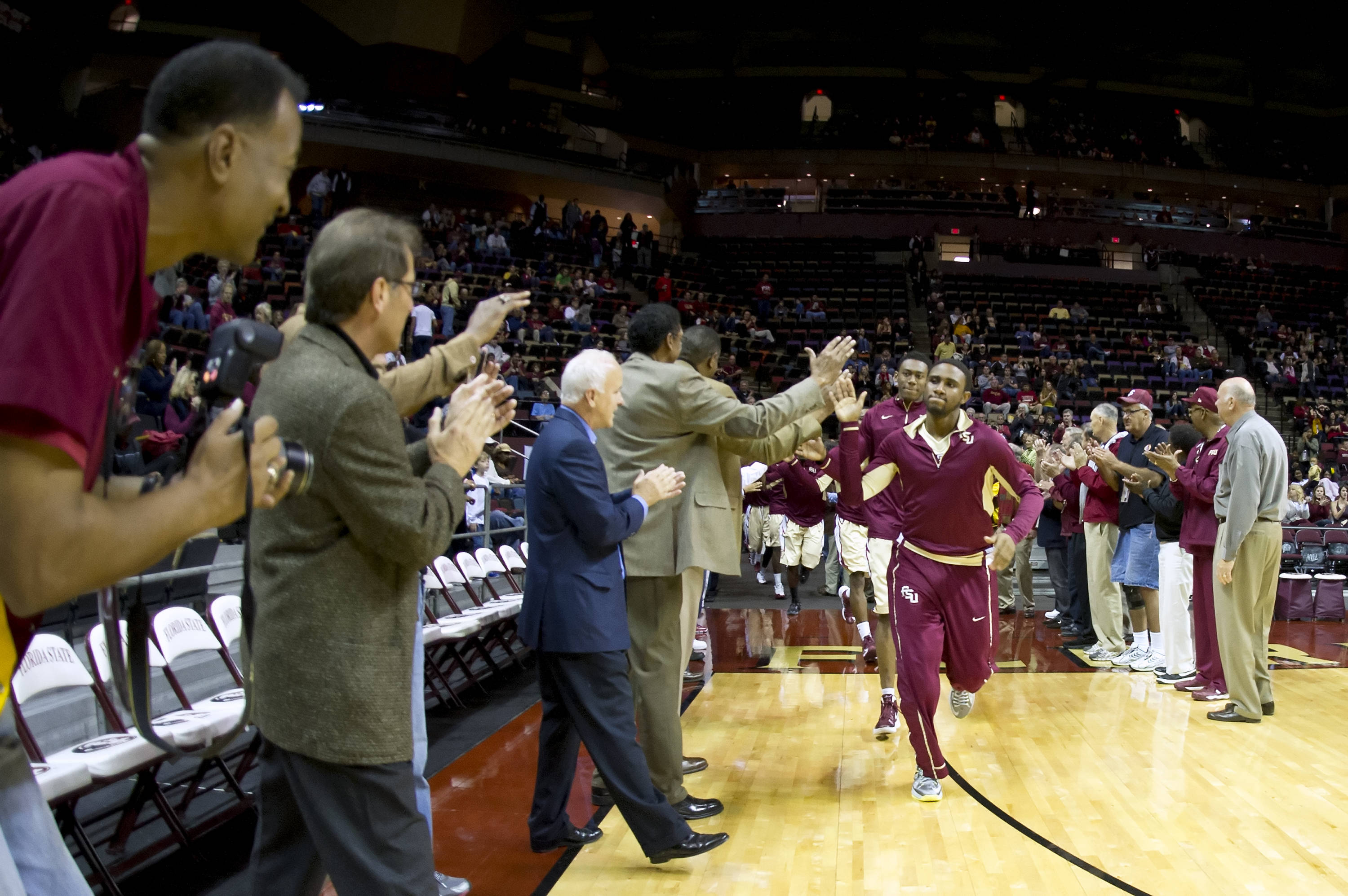 Florida State Men's Basketball alumni greet the team as they take the floor