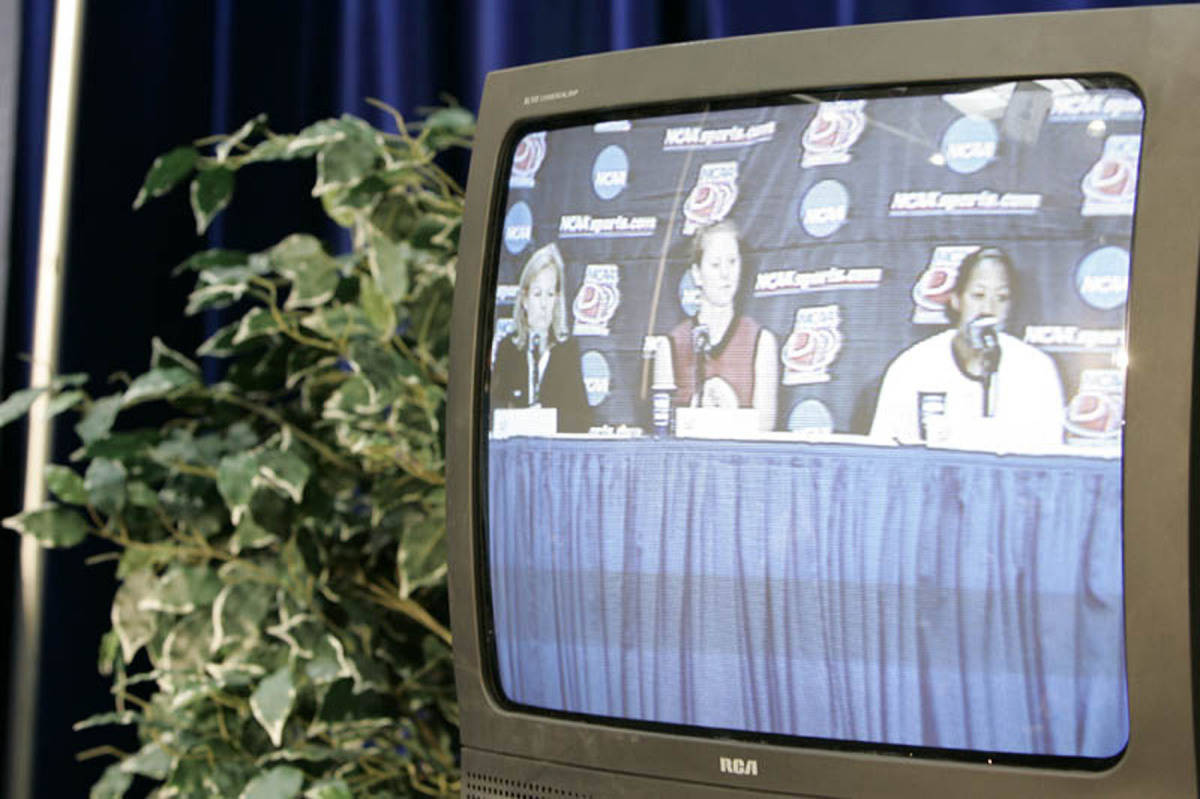 The press conference is shown on TV monitors.