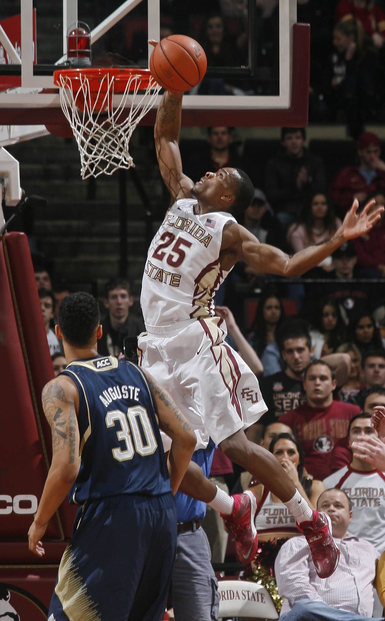 Jan 21, 2014; Tallahassee, FL, USA; Florida State Seminoles guard Aaron Thomas (25) grabs a rebound as Notre Dame Fighting Irish forward Zach Auguste (30) watches in the second half at the Donald L. Tucker Center. The Florida State Seminoles beat the Notre Dame Fighting Irish 76-74. Mandatory Credit: Phil Sears-USA TODAY Sports