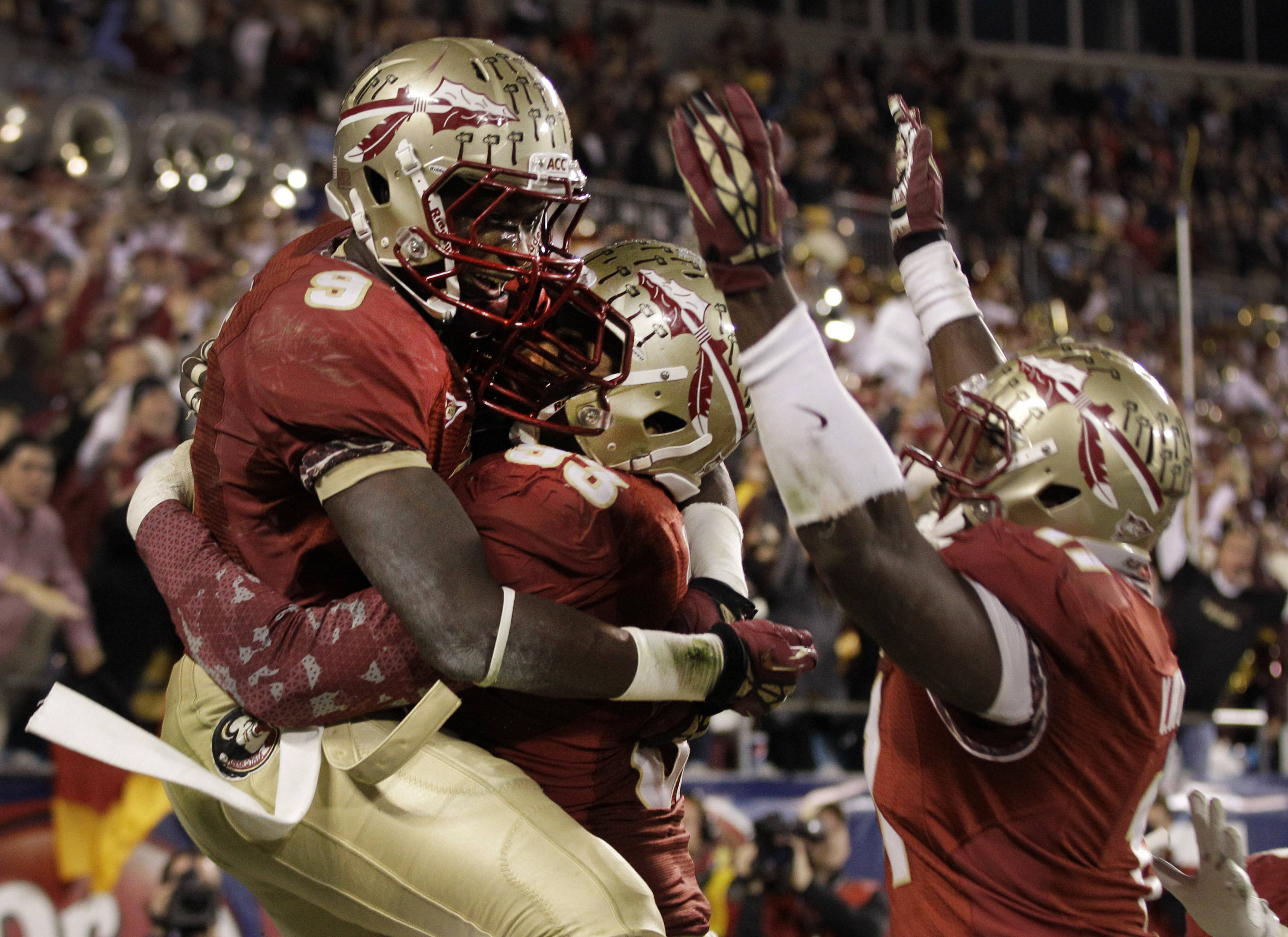 Florida State's Karlos Williams (9) celebrates his interception of a Georgia Tech pass with Everett Dawkins (93) and Vince Williams (11) during the second half. (AP Photo/Chuck Burton)