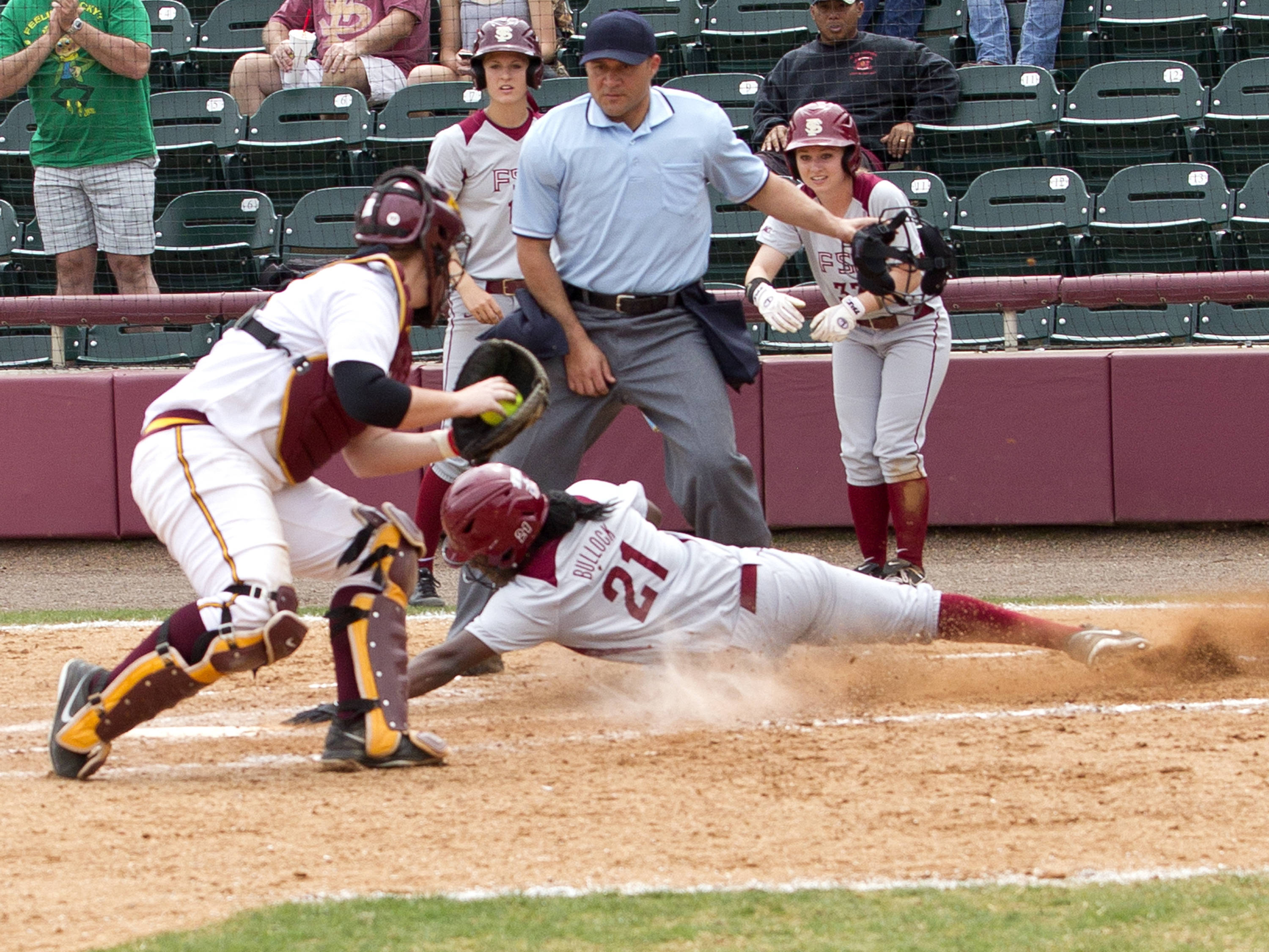 Morgan Bullock (21) with a run scoring hook slide, FSU vs Minnesota, 03/17/13. (Photo by Steve Musco)