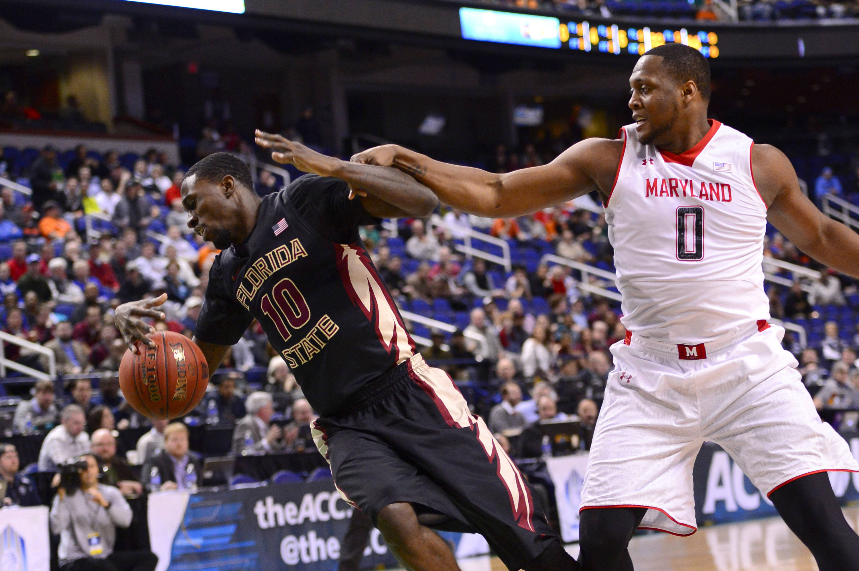 Florida State Seminoles forward Okaro White (10) and Maryland Terrapins forward Charles Mitchell (0) fight for the ball in the first half in the second round of the ACC college basketball tournament at Greensboro Coliseum. Mandatory Credit: Bob Donnan-USA TODAY Sports