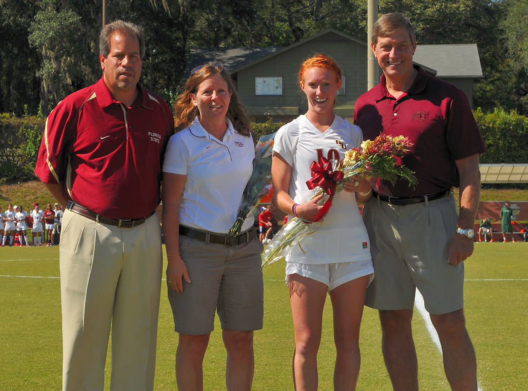 Head coach Mark Krikorian and Director of Athletics Randy Spetman with Tori Huster and her mom on senior day.