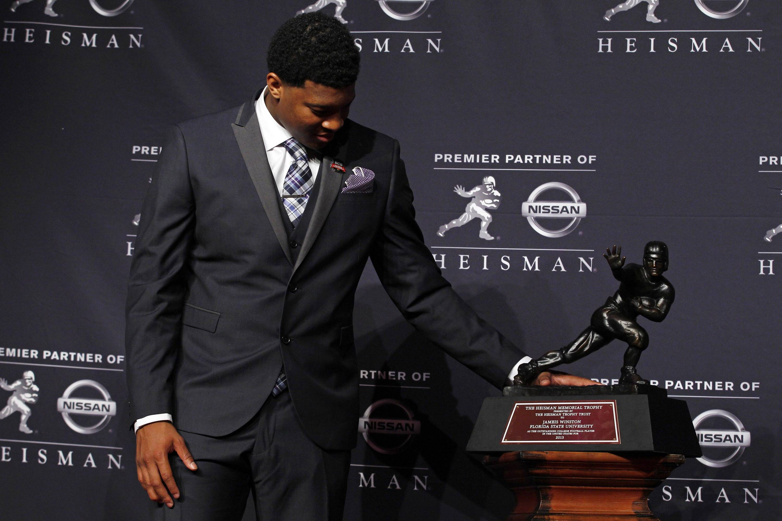 Dec 14, 2013; New York, NY, USA; Seminoles quarterback Jameis Winston looks at the trophy after being awarded the 2013 Heisman Trophy. Adam Hunger-USA TODAY Sports