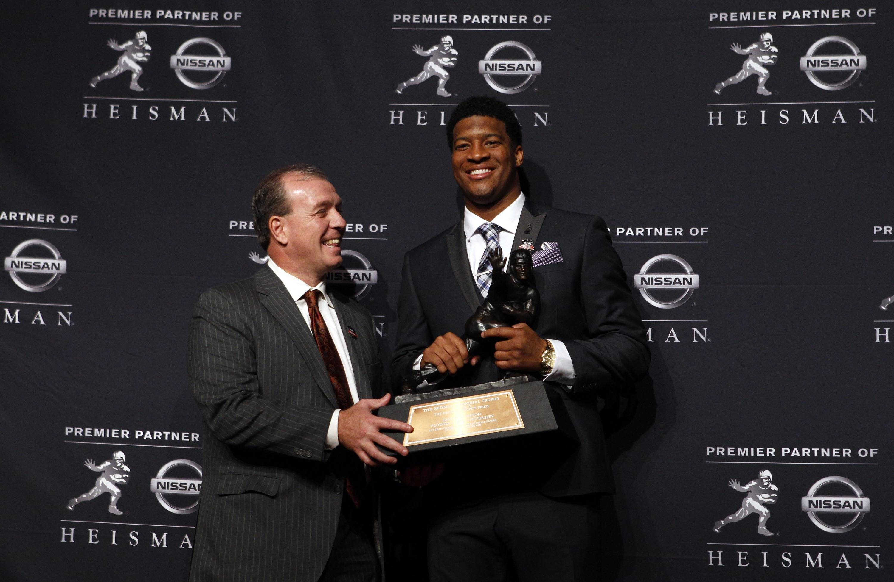 Dec 14, 2013; New York, NY, USA; Seminoles quarterback Jameis Winston poses with head coach Jimbo Fisher after being awarded the 2013 Heisman Trophy. Adam Hunger-USA TODAY Sports