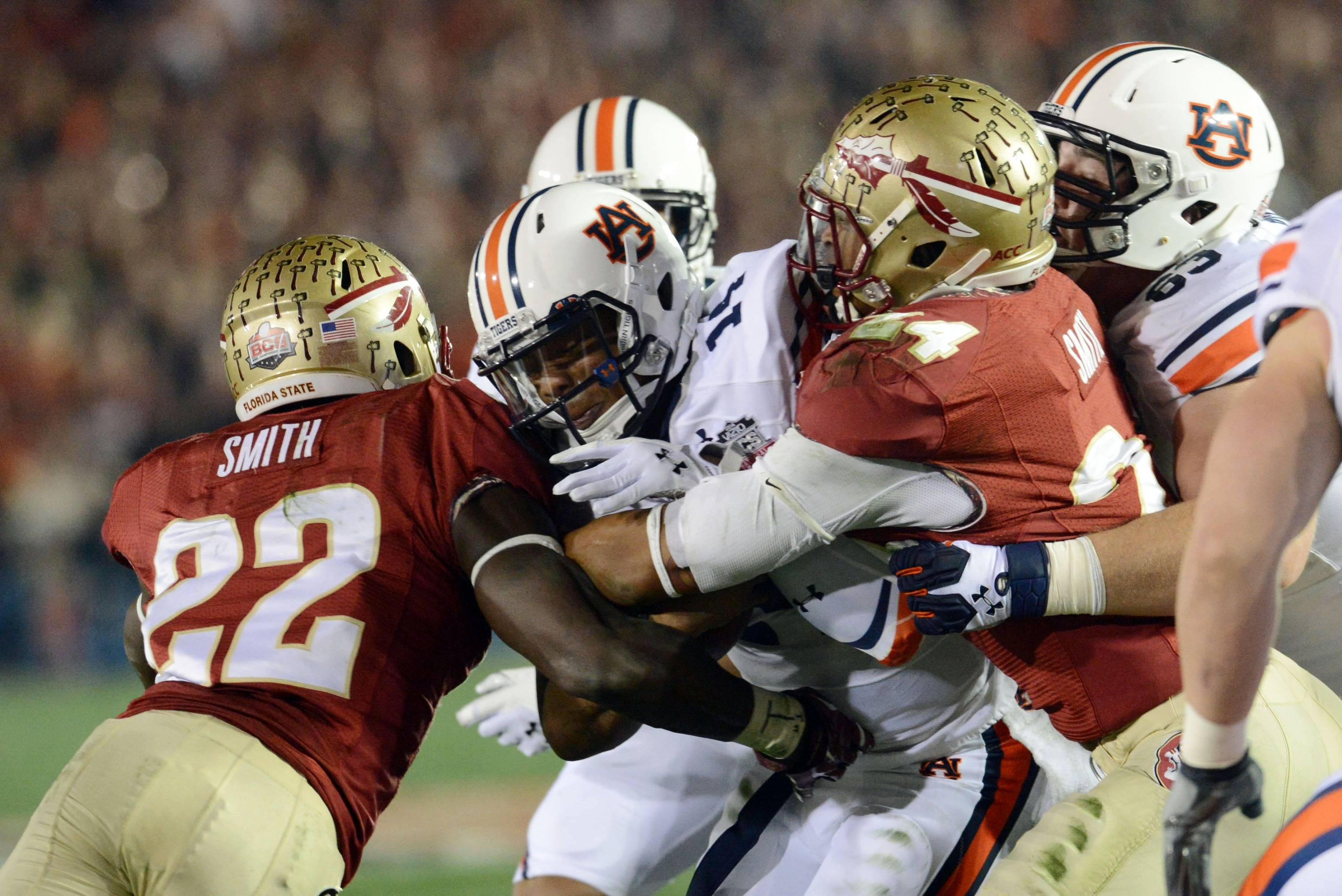 Jan 6, 2014; Pasadena, CA, USA; Auburn Tigers quarterback Nick Marshall (14) is tackled by Florida State Seminoles linebacker Telvin Smith (22) and linebacker Terrance Smith (24) during the first half of the 2014 BCS National Championship game at the Rose Bowl.  Mandatory Credit: Jayne Kamin-Oncea-USA TODAY Sports