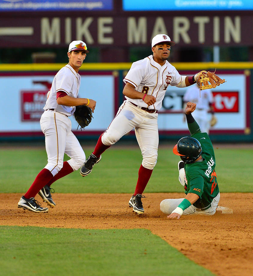 Justin Gonzalez and Devon Travis turn a double play.