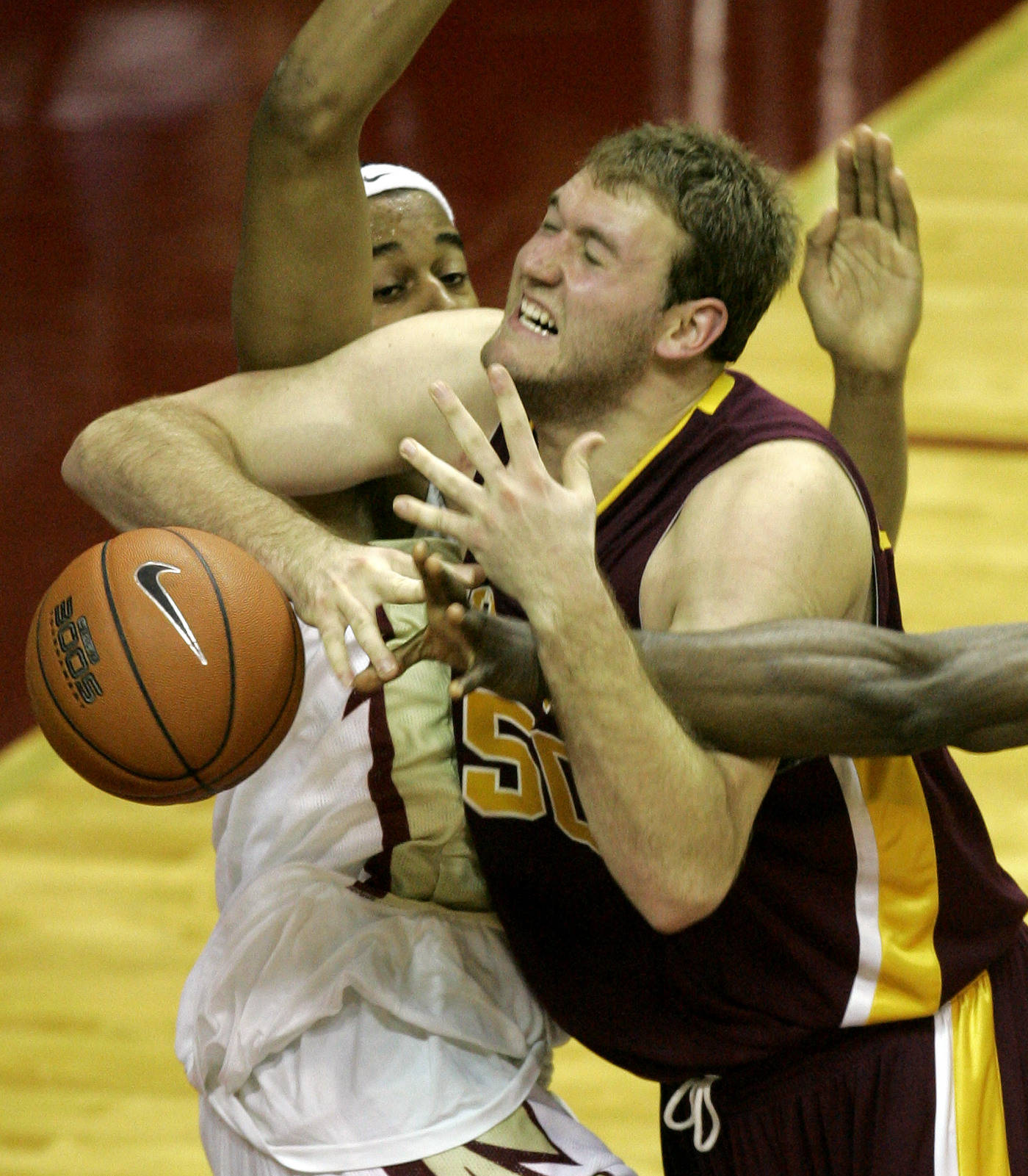 Minnesota's Spencer Tollackson is fouled by Florida State's Julian Vaughn and Uche Echefu during the second half.