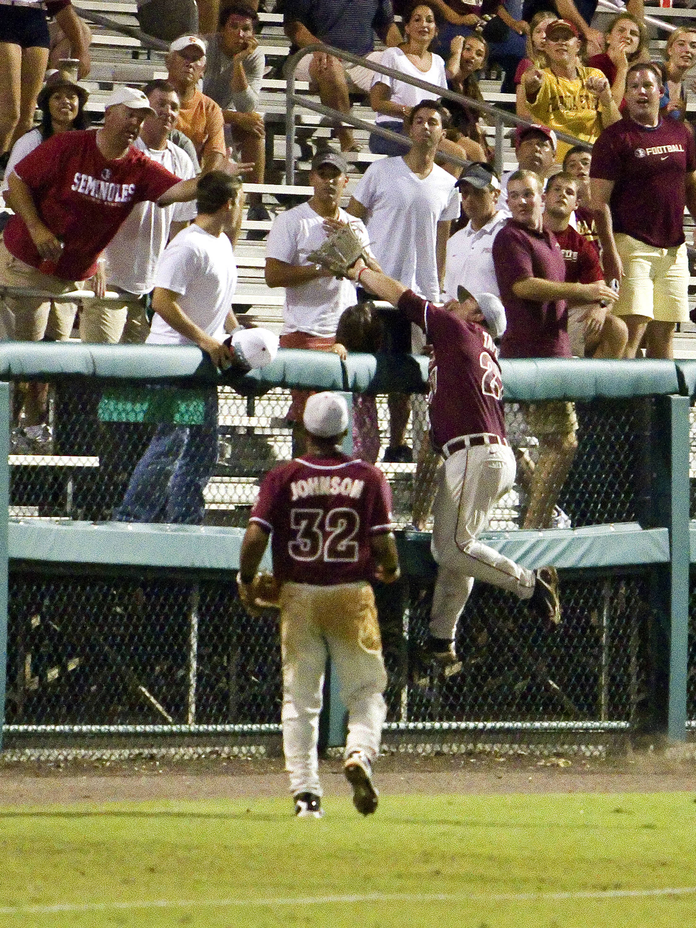 Outfielder Stuart Tapley (27) climbing the fence to attempt a catch