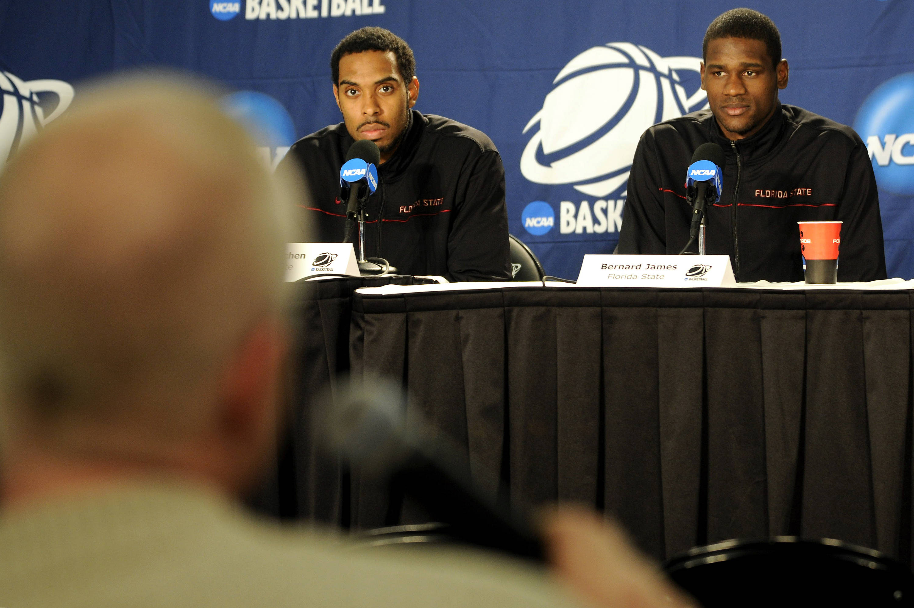 A reporter asks Derwin Kitchen and Bernard James a question during the Seminoles media session
