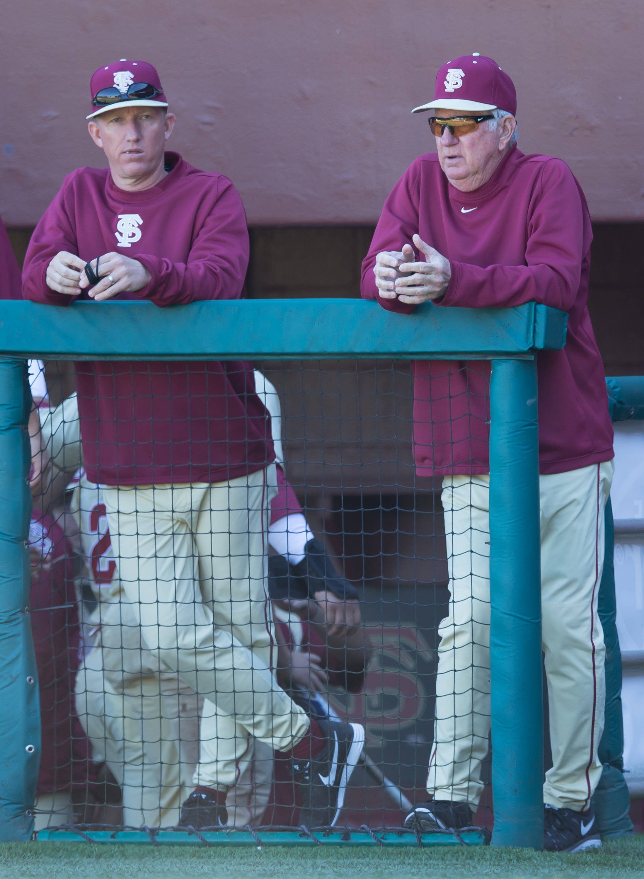 Coaches Mike Bell (22) and Mike Martin (11) watch game action.