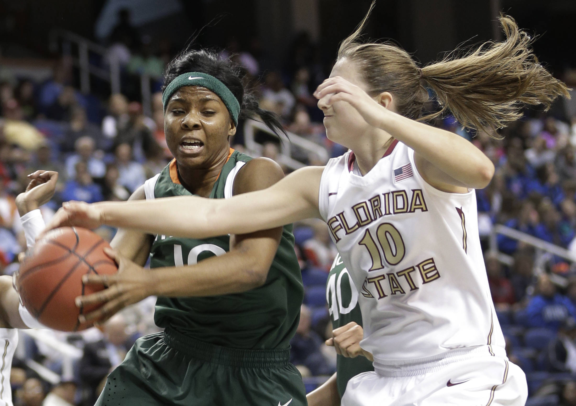 Miami's Michelle Woods, left, and Florida State's Leonor Rodriguez, right, battle for a rebound. (AP Photo/Chuck Burton)
