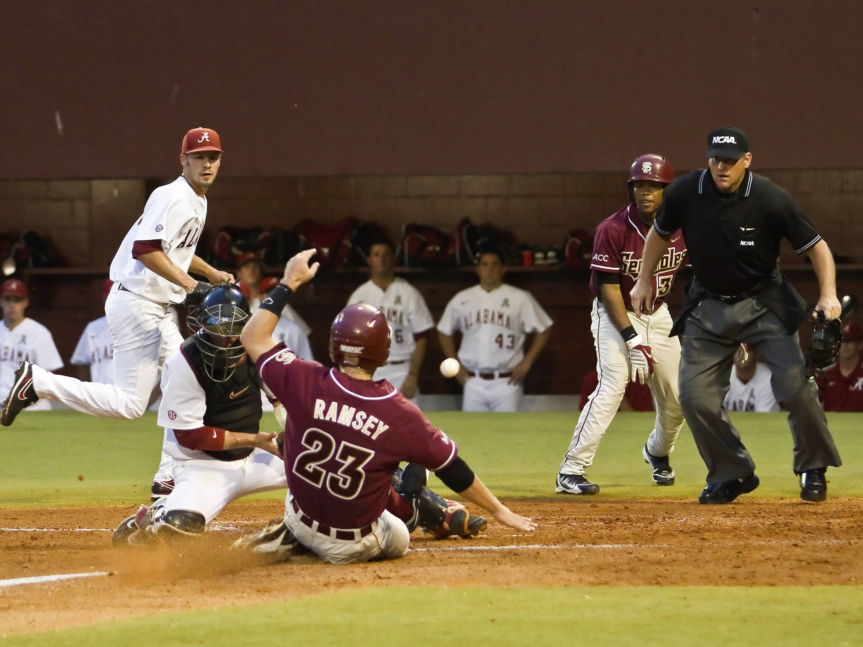 Outfielder James Ramsey (23) disrupting the play at home and scoring