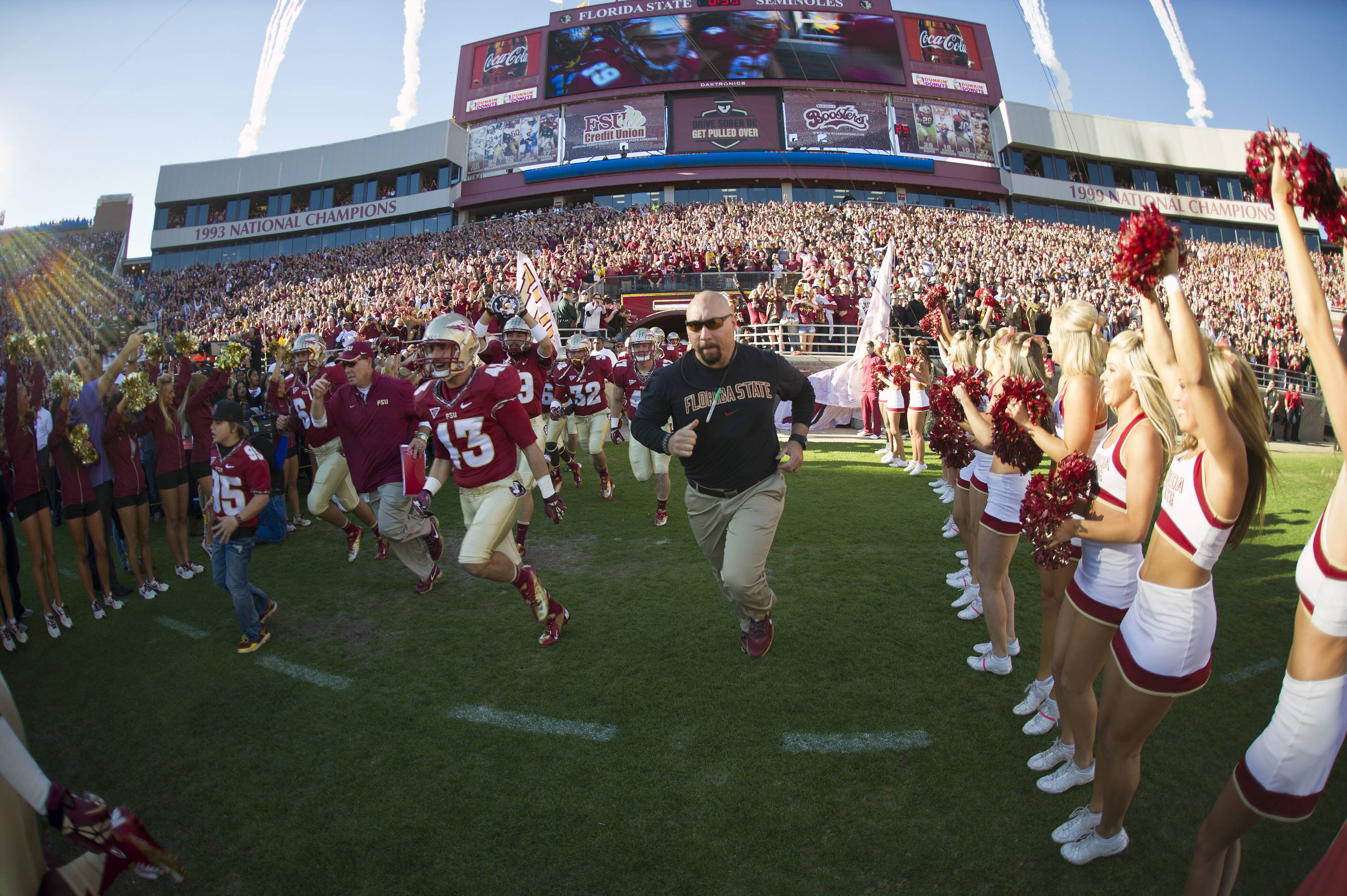 The Seminoles take the field led by Coach Fisher