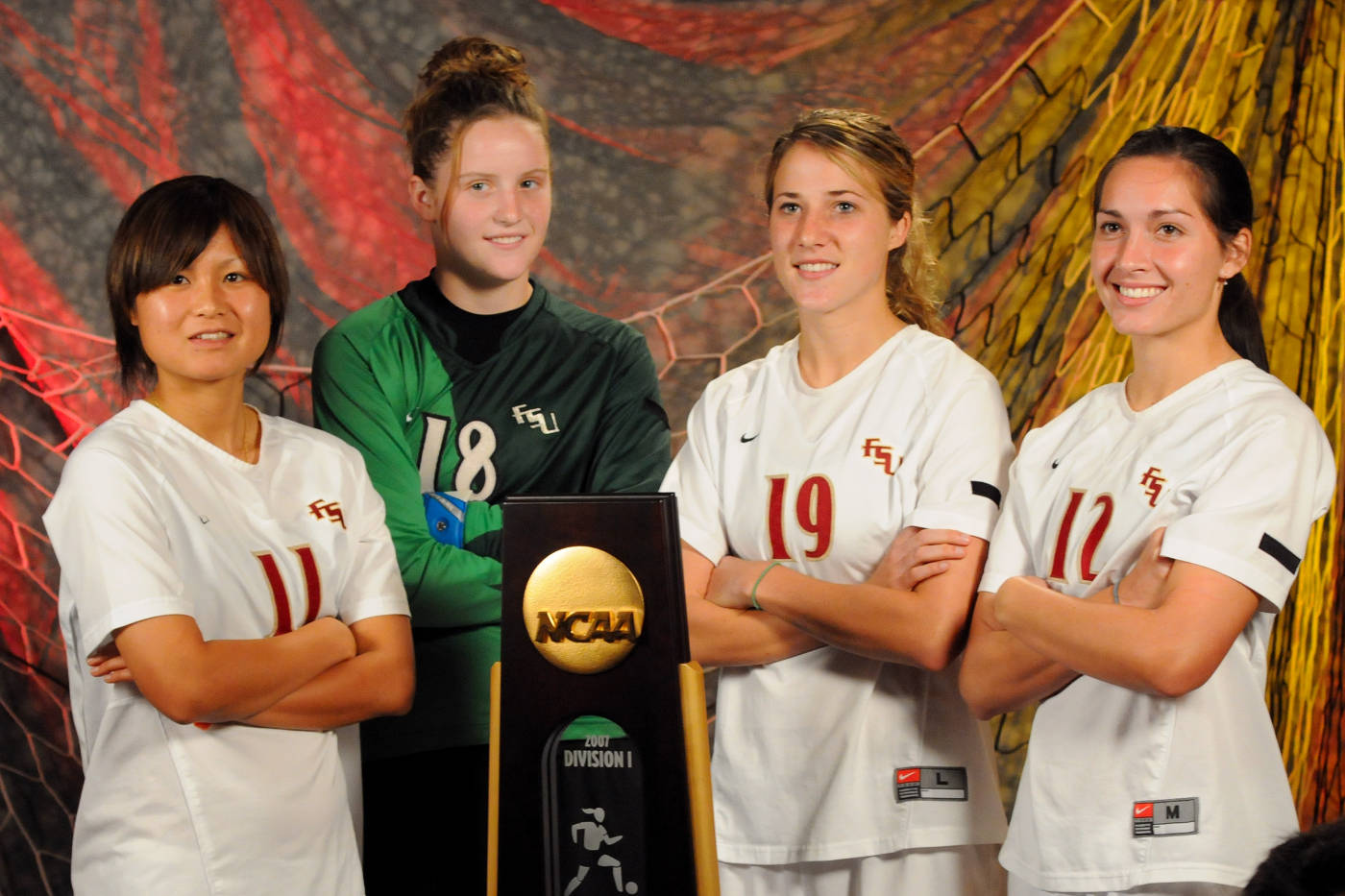Mami Yamaguchi, Erin McNulty, Becky Edwards and Libby Gianeskis take a picture with the National Championship trophy during their interviews with ESPN.