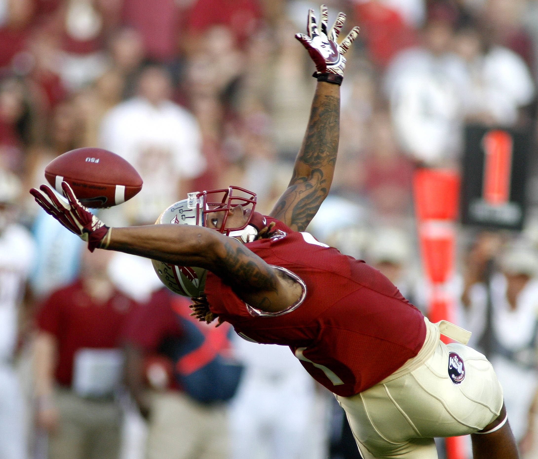 Florida State wide receiver Kelvin Benjamin (1) extends backwards as he attempts to catch a pass during the first quarter. (AP Photo/Phil Sears)